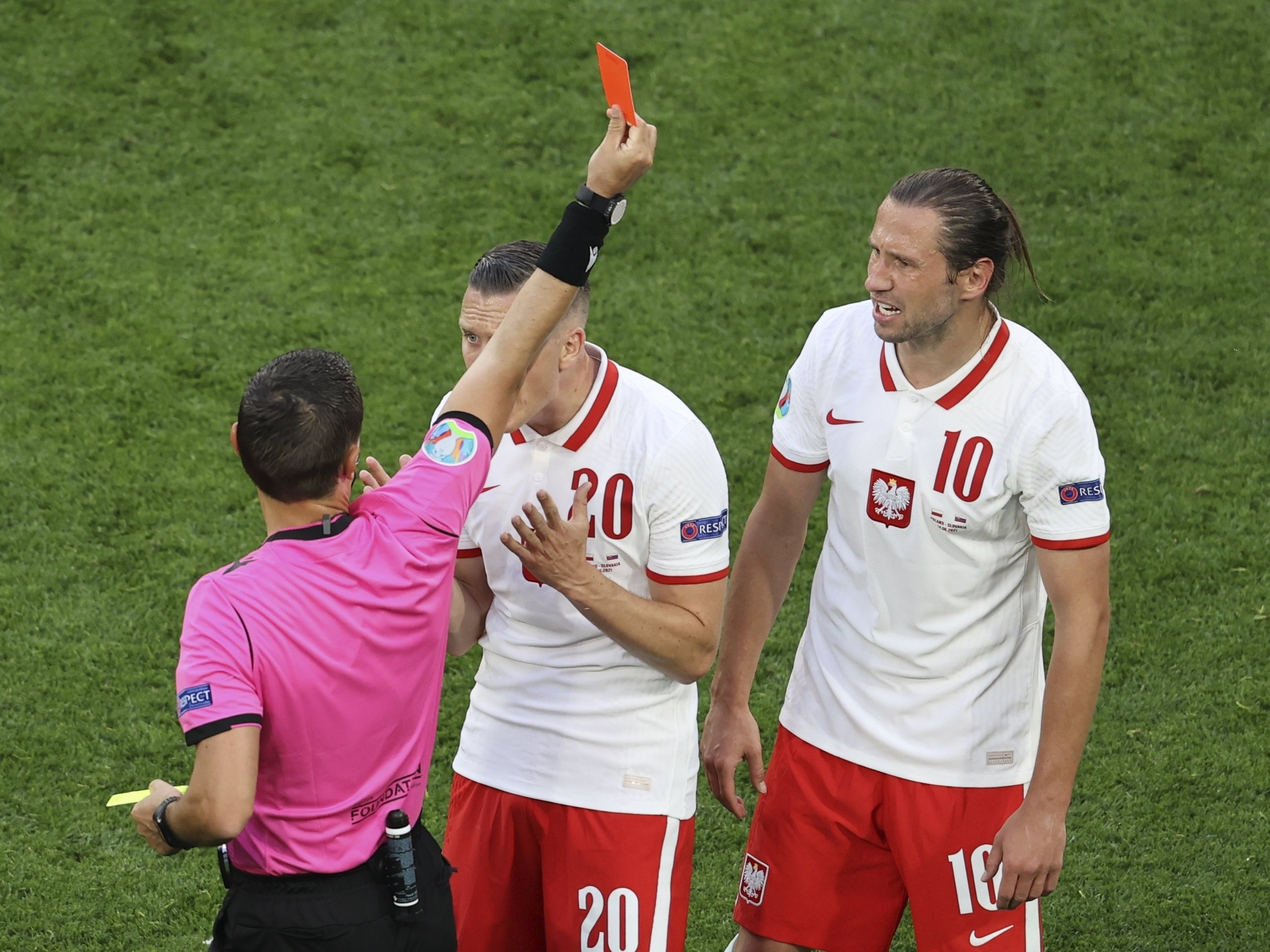 Referee Ovidiu Hategan shows a red card to Poland's Grzegorz Krychowiak (R) during the UEFA Euro 2020 Group E match between Poland and Slovakia at Gazprom Arena Stadium in St. Petersburg, Russia, Monday, June 14, 2021. (Anton Vaganov via AP)