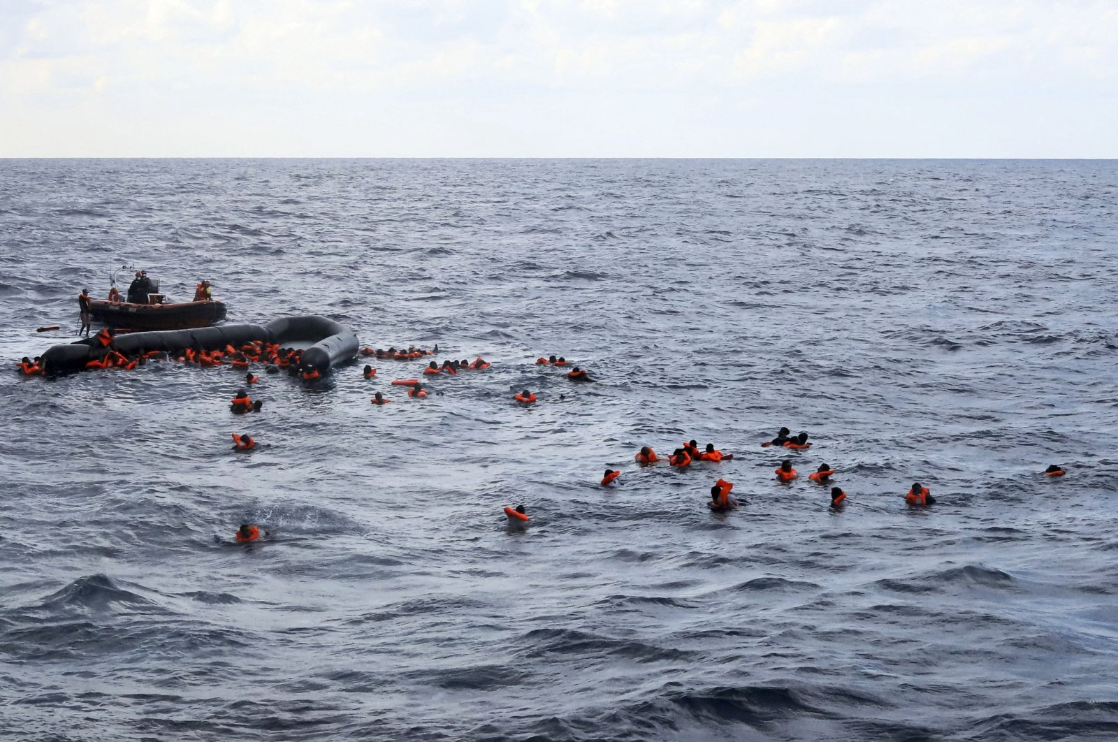 Refugees and migrants are rescued by members of the Spanish NGO Proactiva Open Arms, after leaving Libya trying to reach European soil aboard an overcrowded rubber boat in the Mediterranean Sea, Wednesday, Nov. 11, 2020. (AP File Photo)