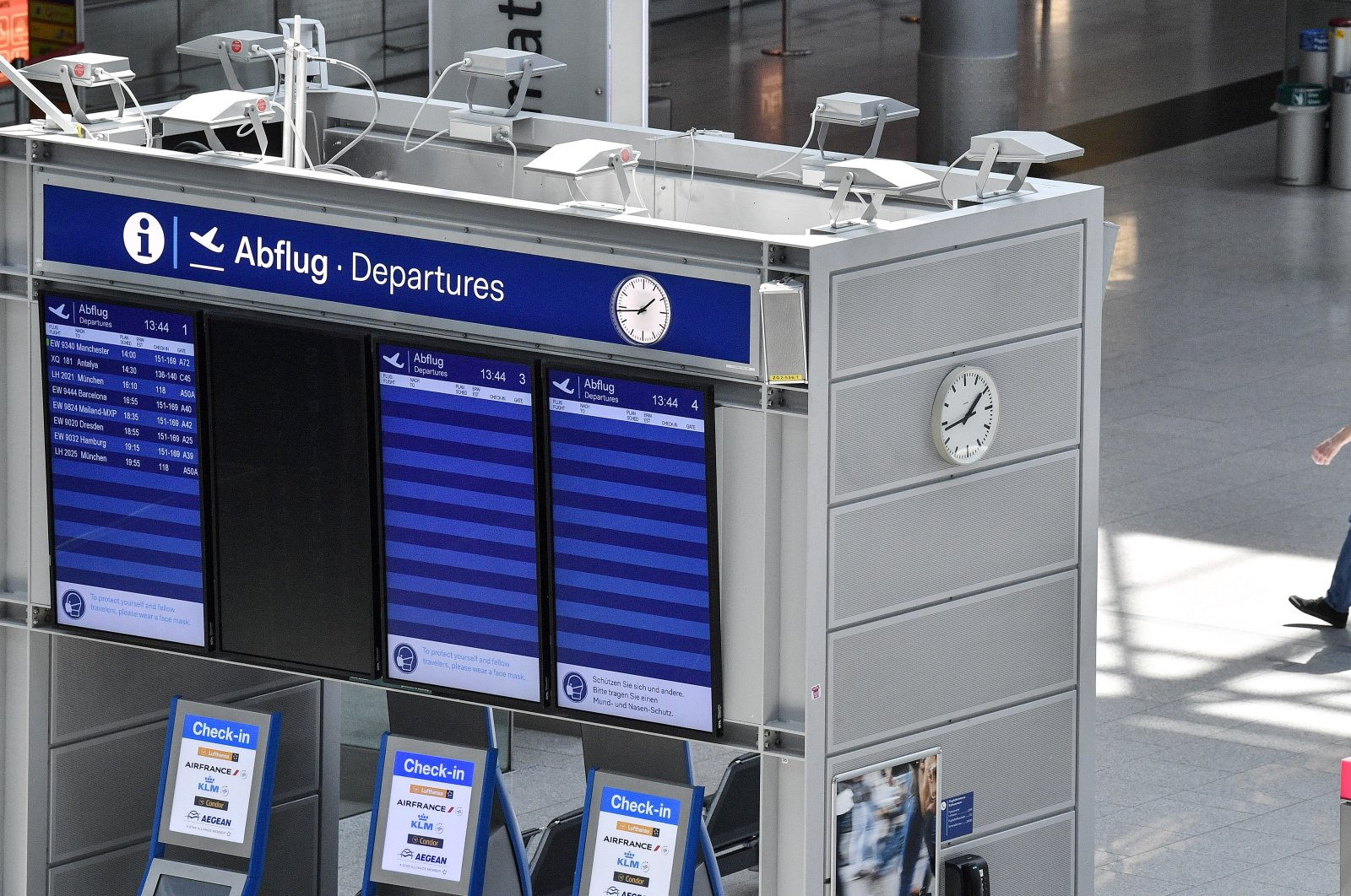 A man passes an empty departure information board at the airport in Duesseldorf, Germany, June 3, 2020. (AP Photo)