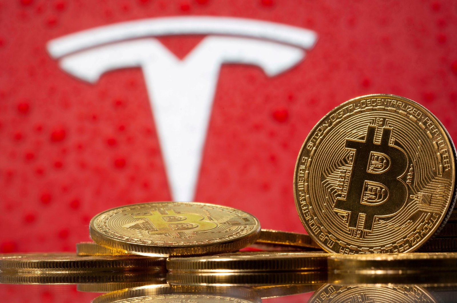 Representations of virtual currency bitcoin are seen in front of Tesla logo in this illustration, Feb. 9, 2021. (Reuters Photo)