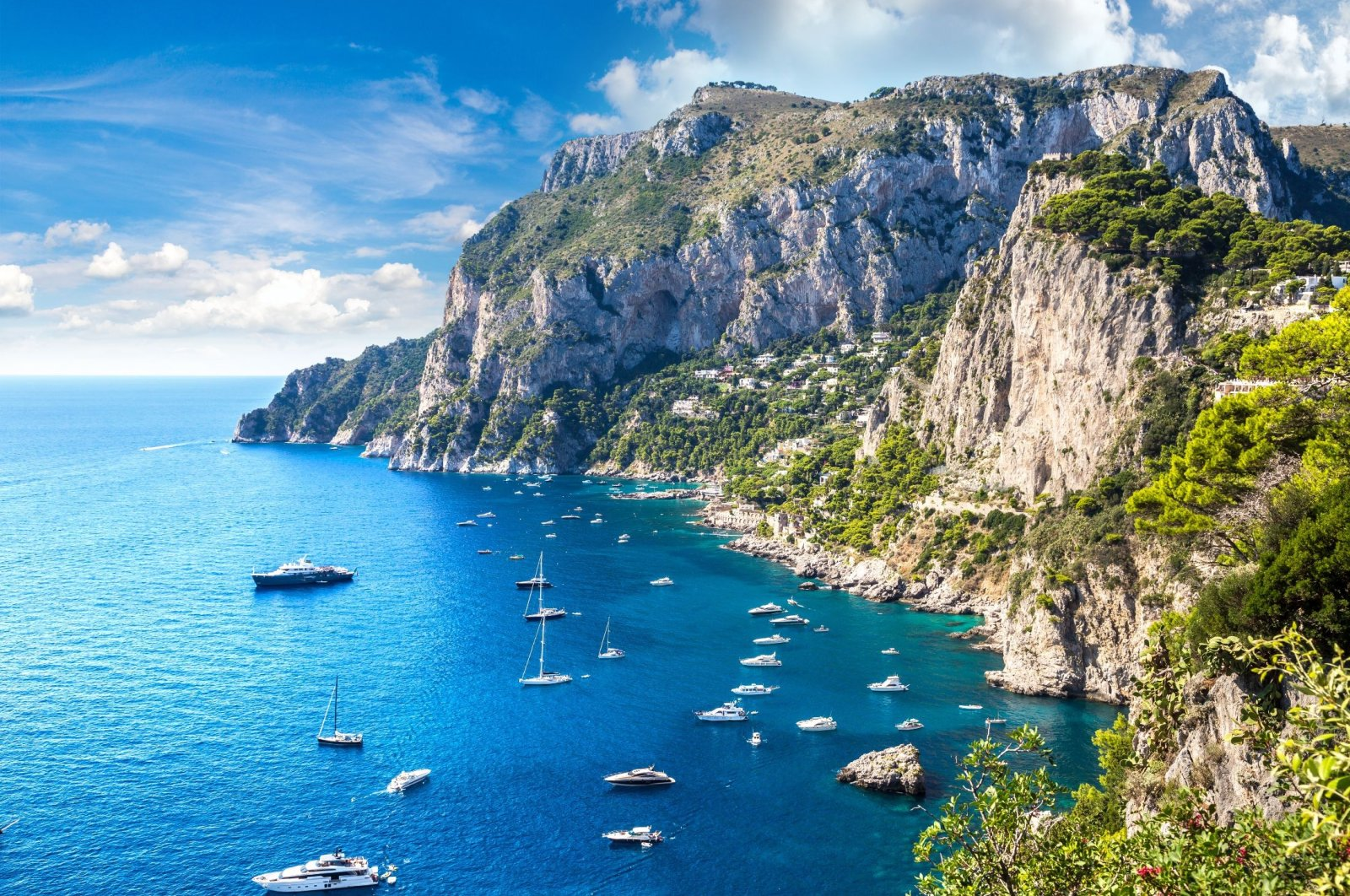 A group of boats float off the shore of the island of Capri, Italy. (Shutterstock Photo)