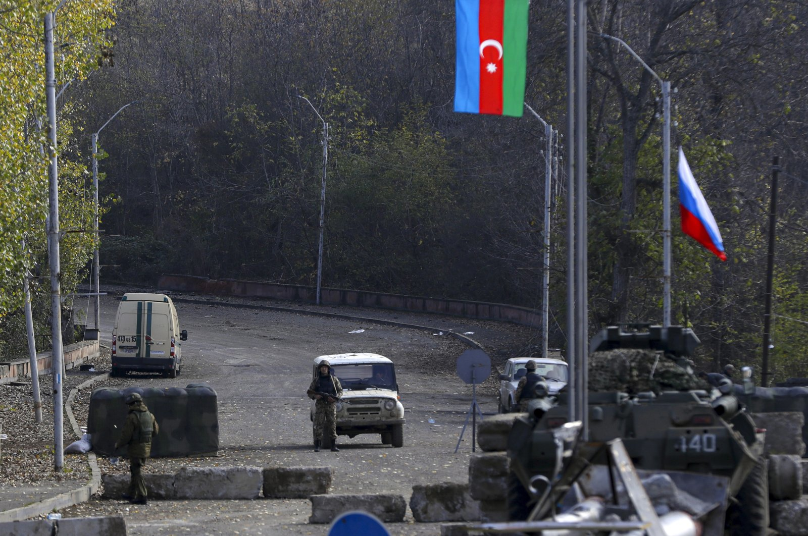 An Azerbaijani soldier (C) stands in front of an off-road car as Russian peacekeepers' military vehicles parked at a checkpoint on the road to Shusha in Nagorno-Karabakh, Nov. 17, 2020. (AP File Photo)