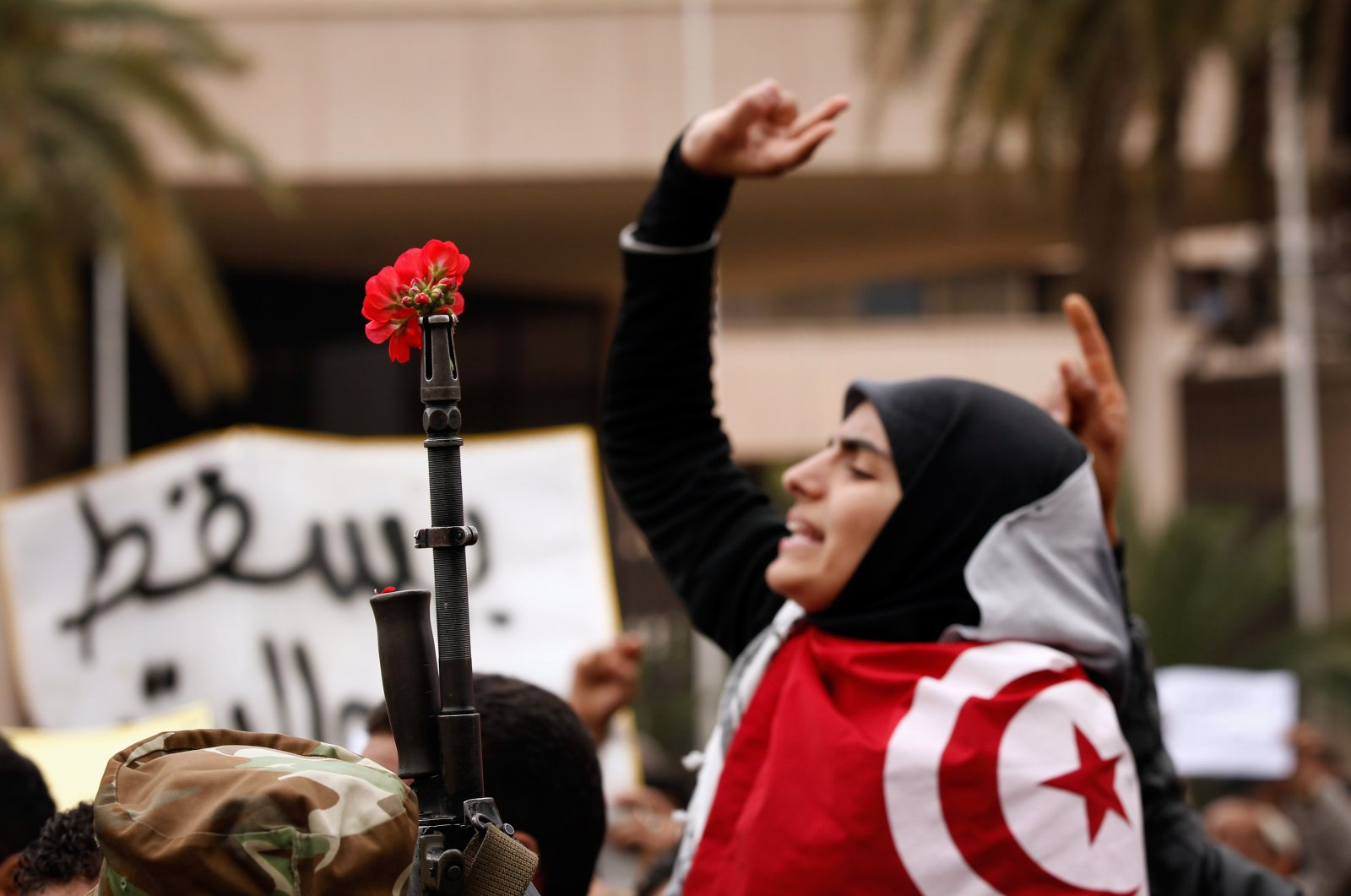 A Tunisian demonstrator makes a peace sign next to a flower in the barrel of a gun during a mass protest for changes in Tunisia's new government, in Tunis, Tunisia, Jan. 20, 2011. (Photo by Getty Images)