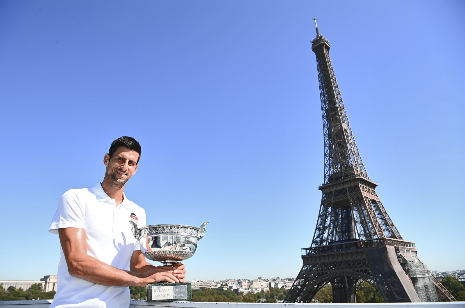 Serbia's Novak Djokovic poses with the trophy in front of the Eiffel tower during a photocall, Paris, France, June 14, 2021. (AP Photo)