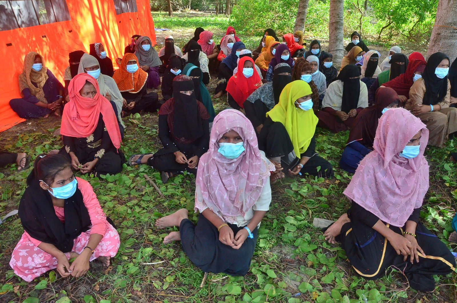 A group of Rohingya refugees, mostly women and children, gather on Pulau Idaman, a small island just off the coast of East Aceh, in northern Sumatra on June 6, 2021, after a group of 81 refugees landed on June 4, in the latest wave of Rohingya arrivals. (AFP Photo)