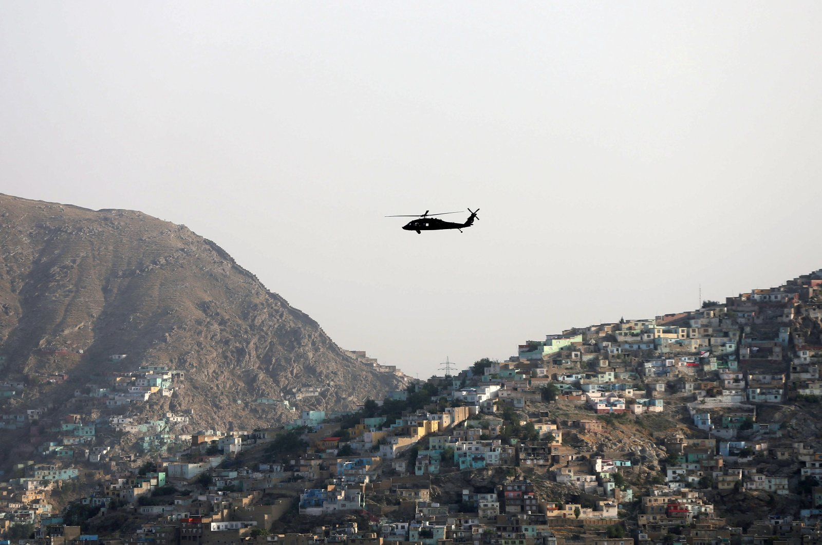 A NATO helicopter flies over the city of Kabul, Afghanistan, June 29. 2020. (Reuters Photo)