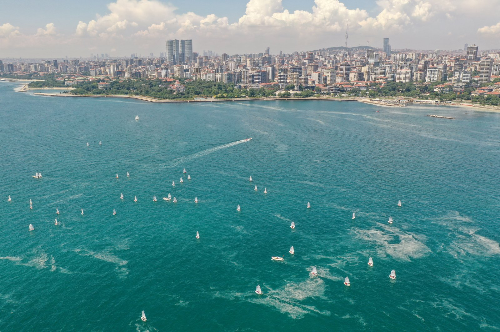 """Aerial view of boats of the Optimist and Laser international classes competing during a race as the sea is partly covered by """"sea snot,"""" a thick slimy layer of the organic matter also known as marine mucilage, spreading through the Sea of Marmara and posing a threat to marine life and the fishing industry, Istanbul, Turkey June 13, 2021. (Reuters Photo)"""