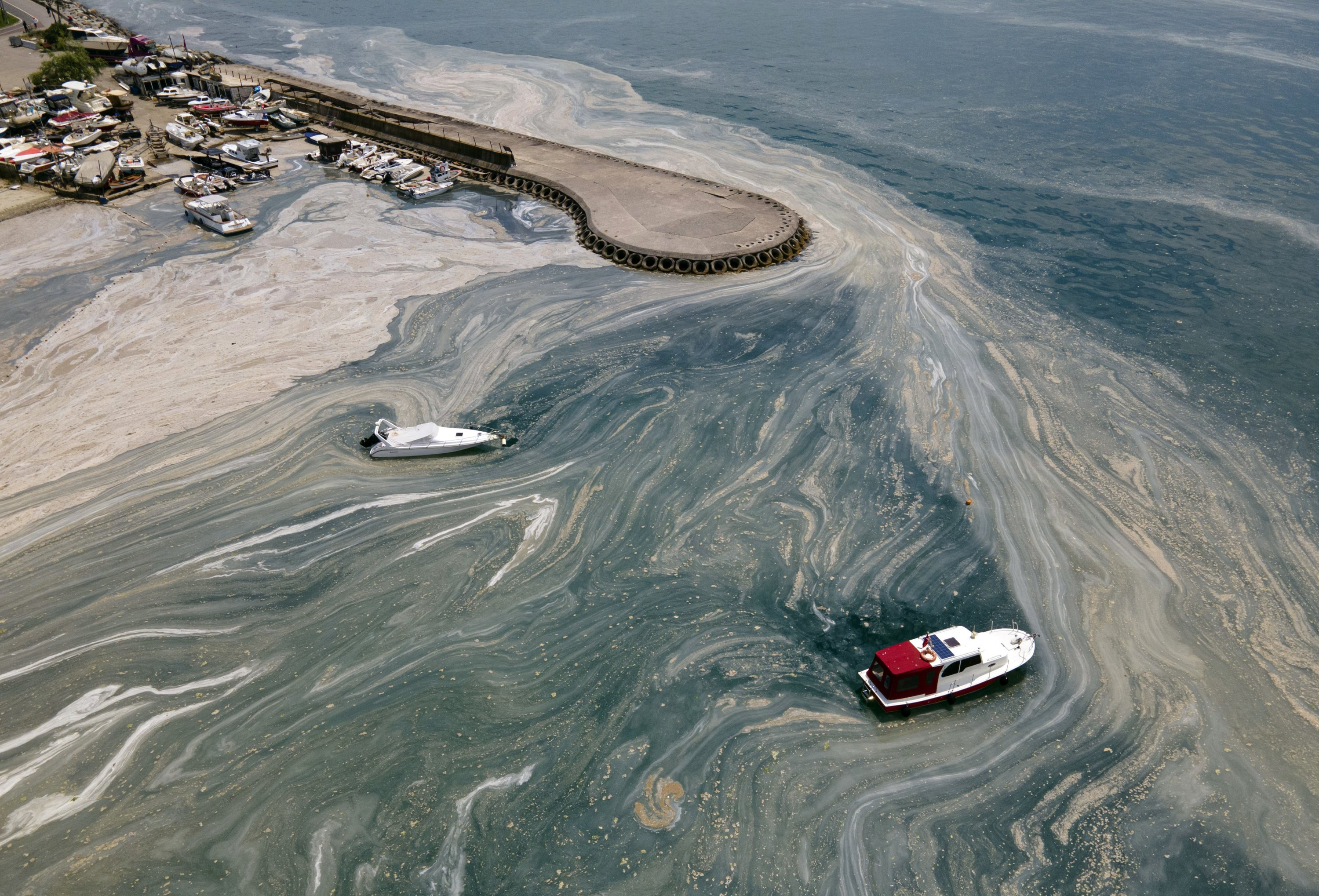 Boats wade in a huge mass of marine mucilage in the Marmara Sea near the Caddebostan shore, on the Asian side of Istanbul, Turkey, June 7, 2021. (AP Photo)