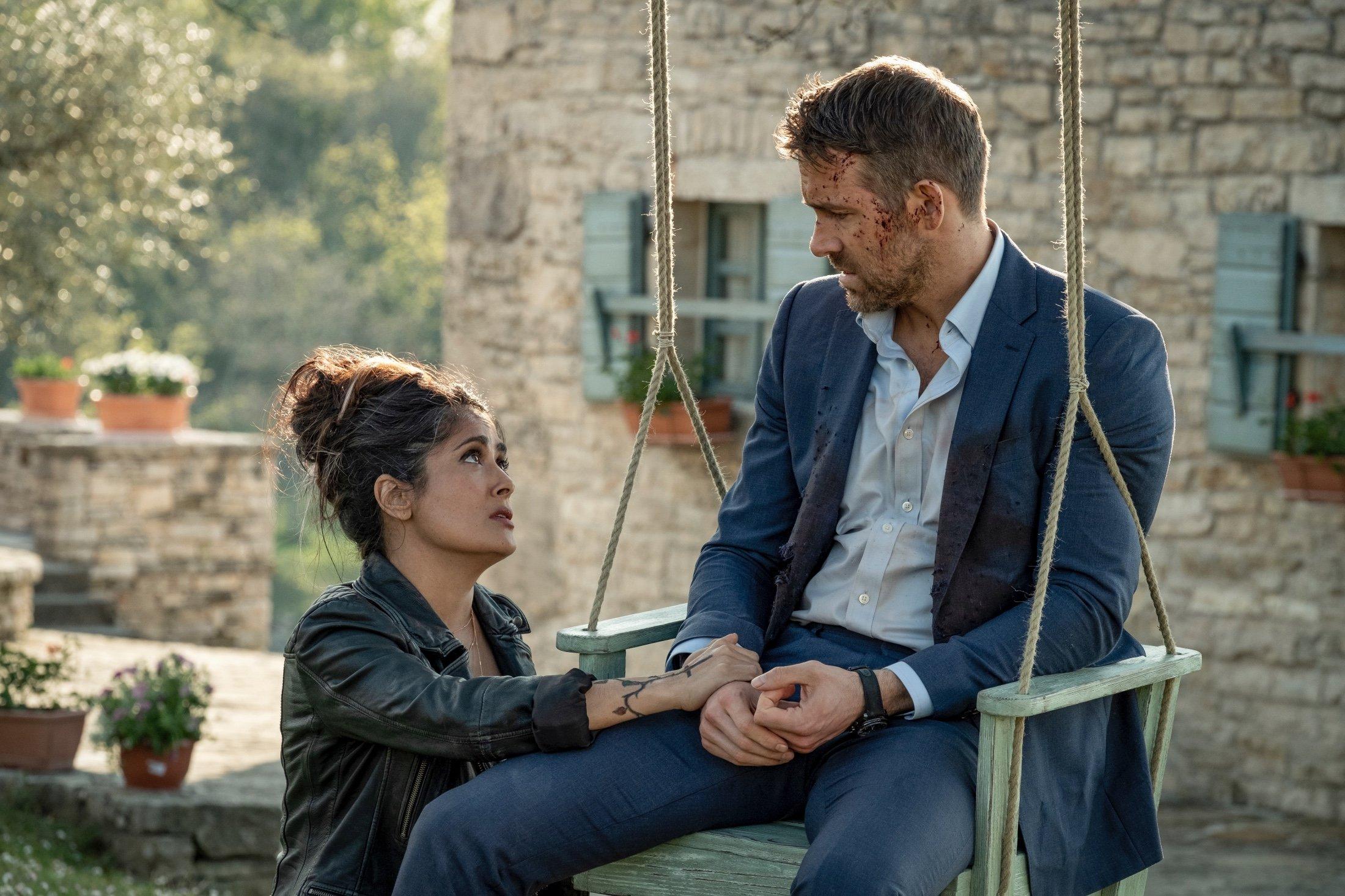 Salma Hayek (L) consolesRyan Reynolds, in a scene from the movie, 'The Hitman's Wife's Bodyguard.' (Lionsgate via AP)