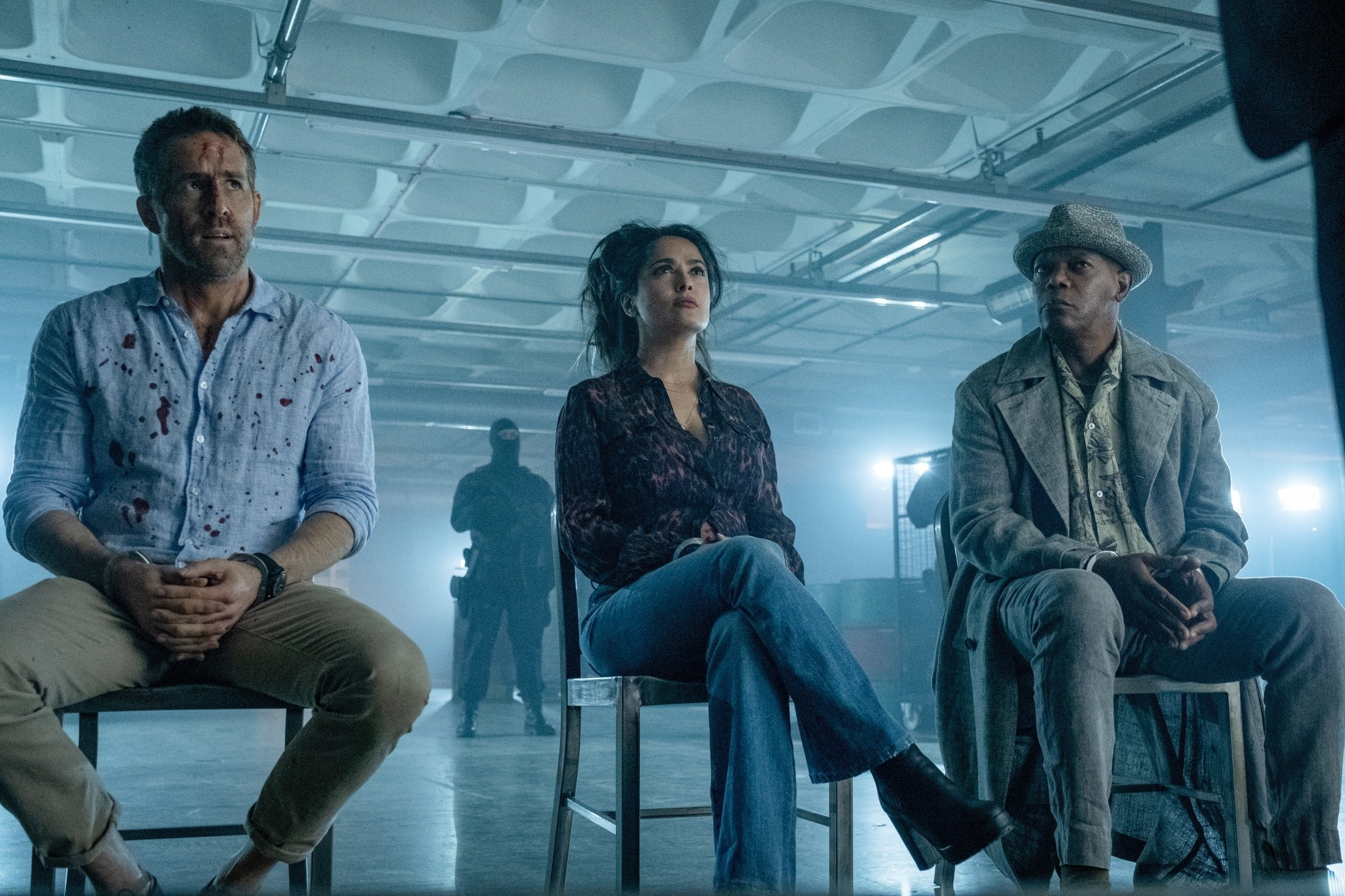 Ryan Reynolds (L), Salma Hayek (C) and Samuel L. Jackson sit together in handcuffs, in a scene from the movie, 'The Hitman's Wife's Bodyguard.' (Lionsgate via AP)