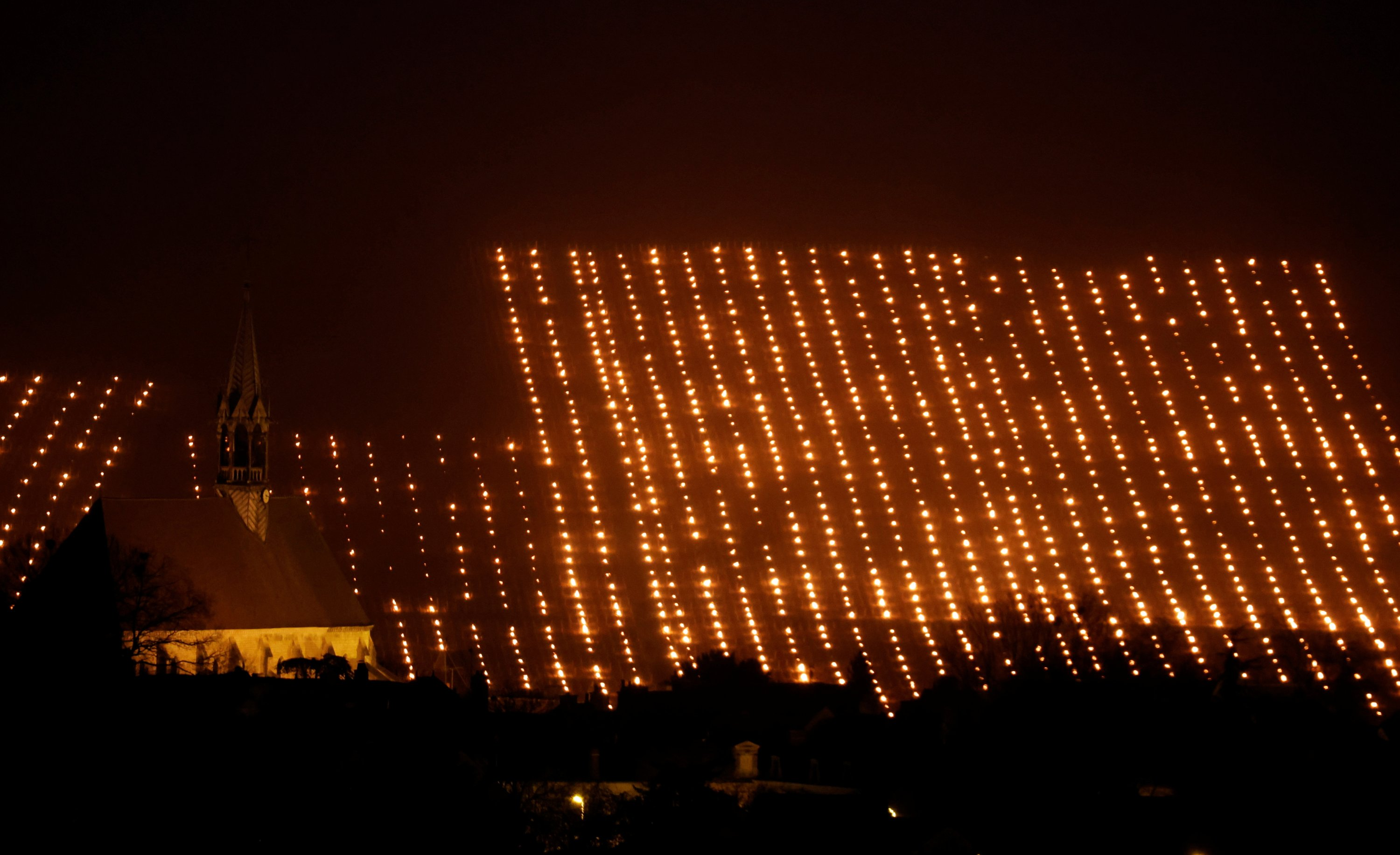 Heaters are lit early in the morning to protect vineyards from frost damage outside Chablis, France, April 7, 2021. (Reuters Photo)
