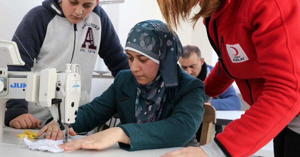 A Red Crescent worker shows a Syrian woman how to sew at a workshop in western Izmir province on Mar. 1, 2019 (AA File Photo)
