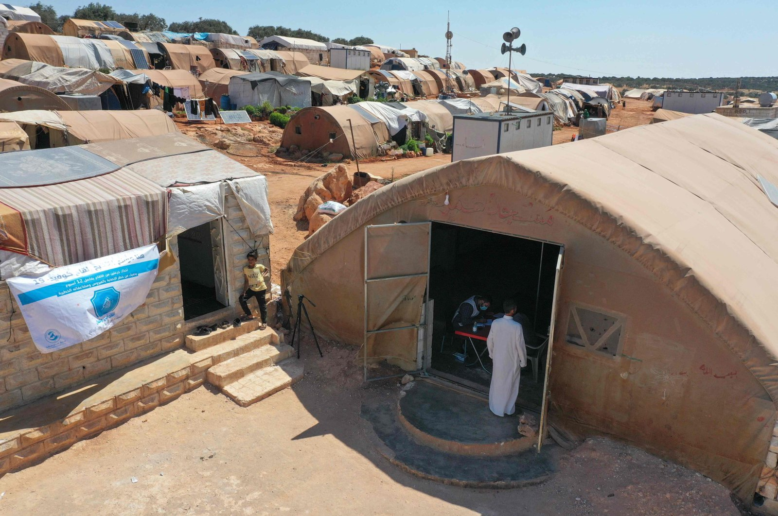 People enter a tent turned into a vaccination center at a camp for the internally displaced near Marret Misrin town, in northwestern Syria's Idlib, Syria, June 14, 2021. (AFP Photo)