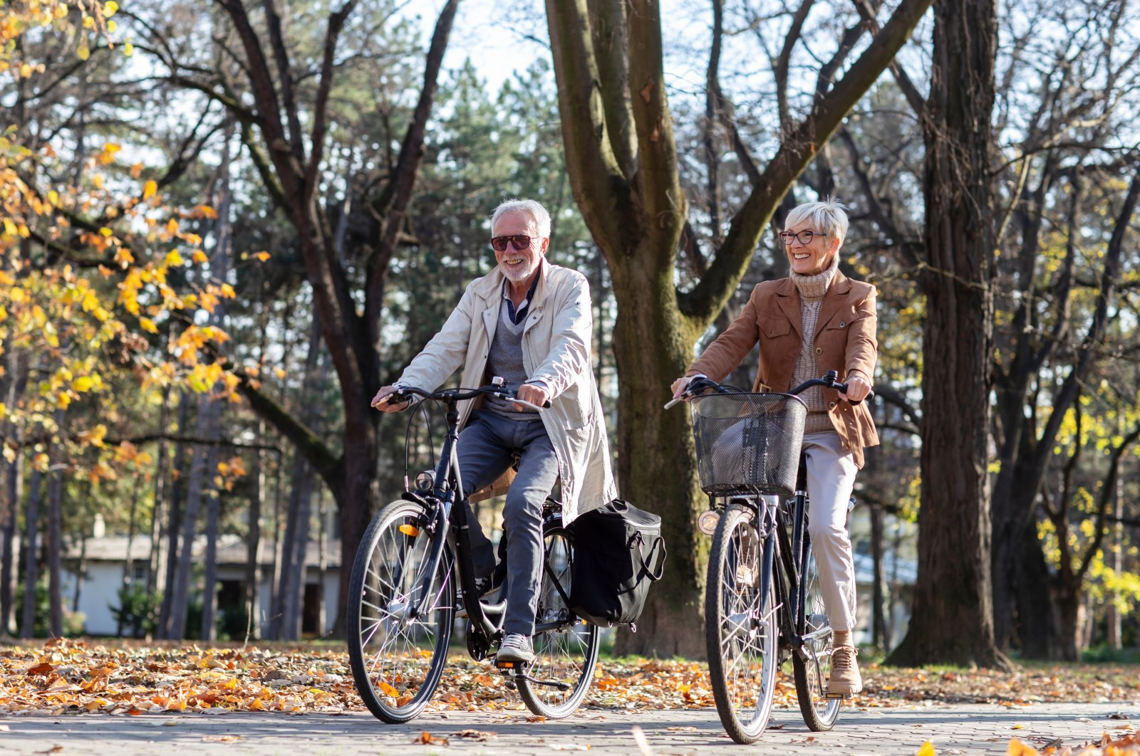 A mature fit couple ride bicycles in a public park. (Shutterstock Photo)