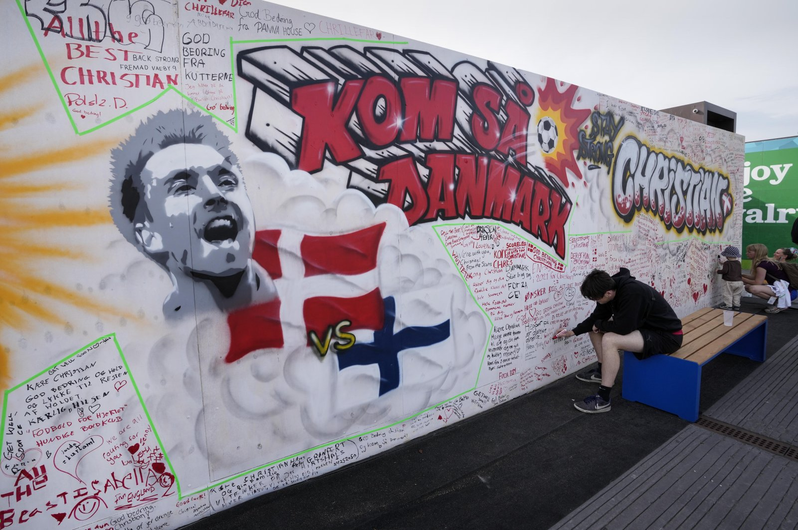 People writing well wishes at a graffiti for Danish player Christian Eriksen on a wall at the fan zone in Copenhagen, Denmark, June 14, 2021. (AP Photo)