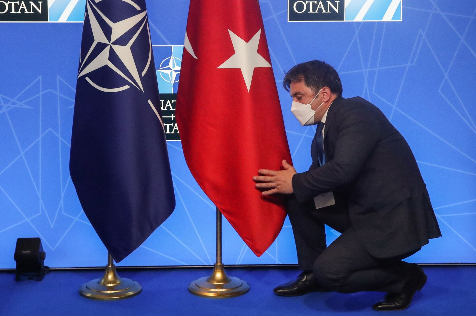 An official adjusts the Turkish flag before a news conference during a NATO summit in Brussels, June 14, 2021. (AFP Photo)
