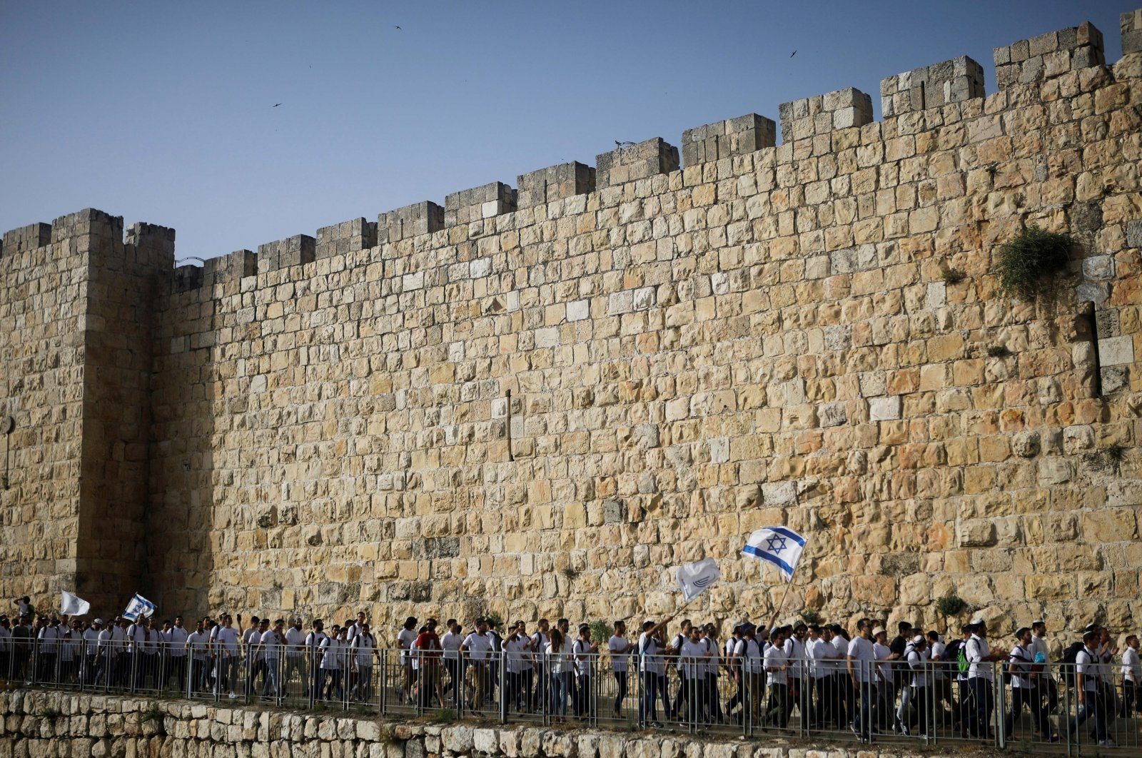 Youth wave Israeli flags during a parade marking Jerusalem Day amid Israeli-Palestinian tension as they march along the walls surrounding East Jerusalem's Old City, occupied Palestine, May 10, 2021. (Reuters Photo)