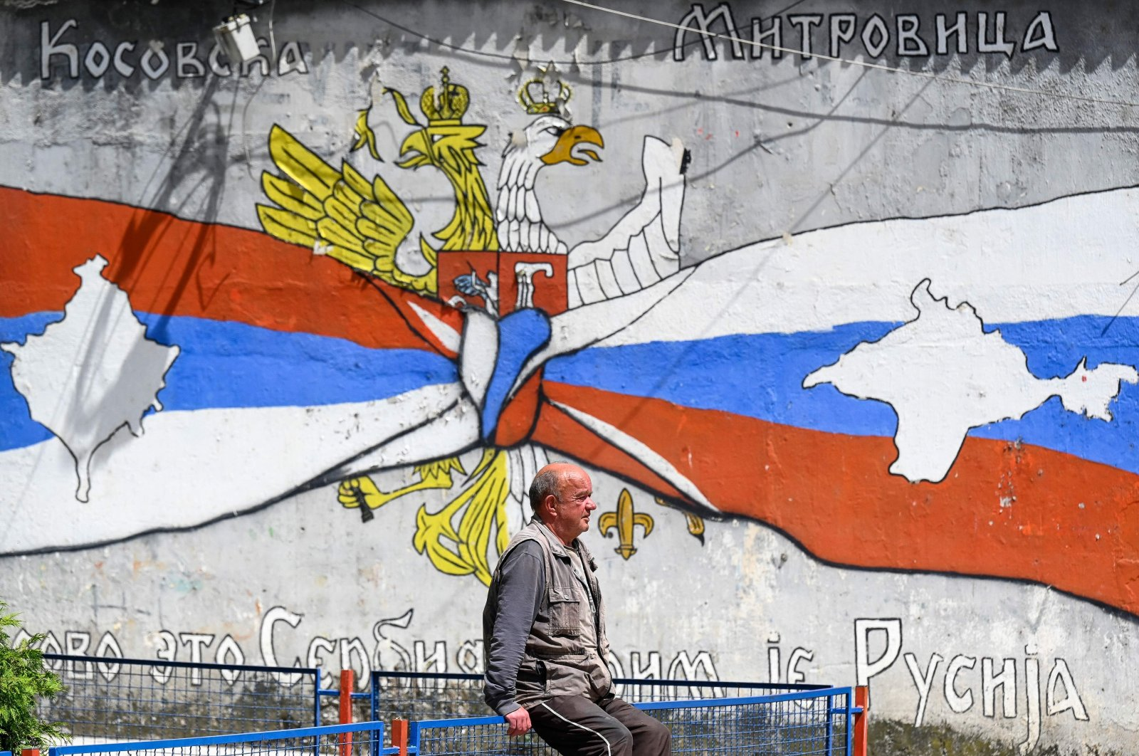 A Kosovo Serb man walks next to a graffiti showing the map of Kosovo in a Serbian flag, on a street in the majority ethnic-Serb northern part of the city of Mitrovica, Kosovo, June 15, 2021. (Photo by Armend Niamani / AFP)