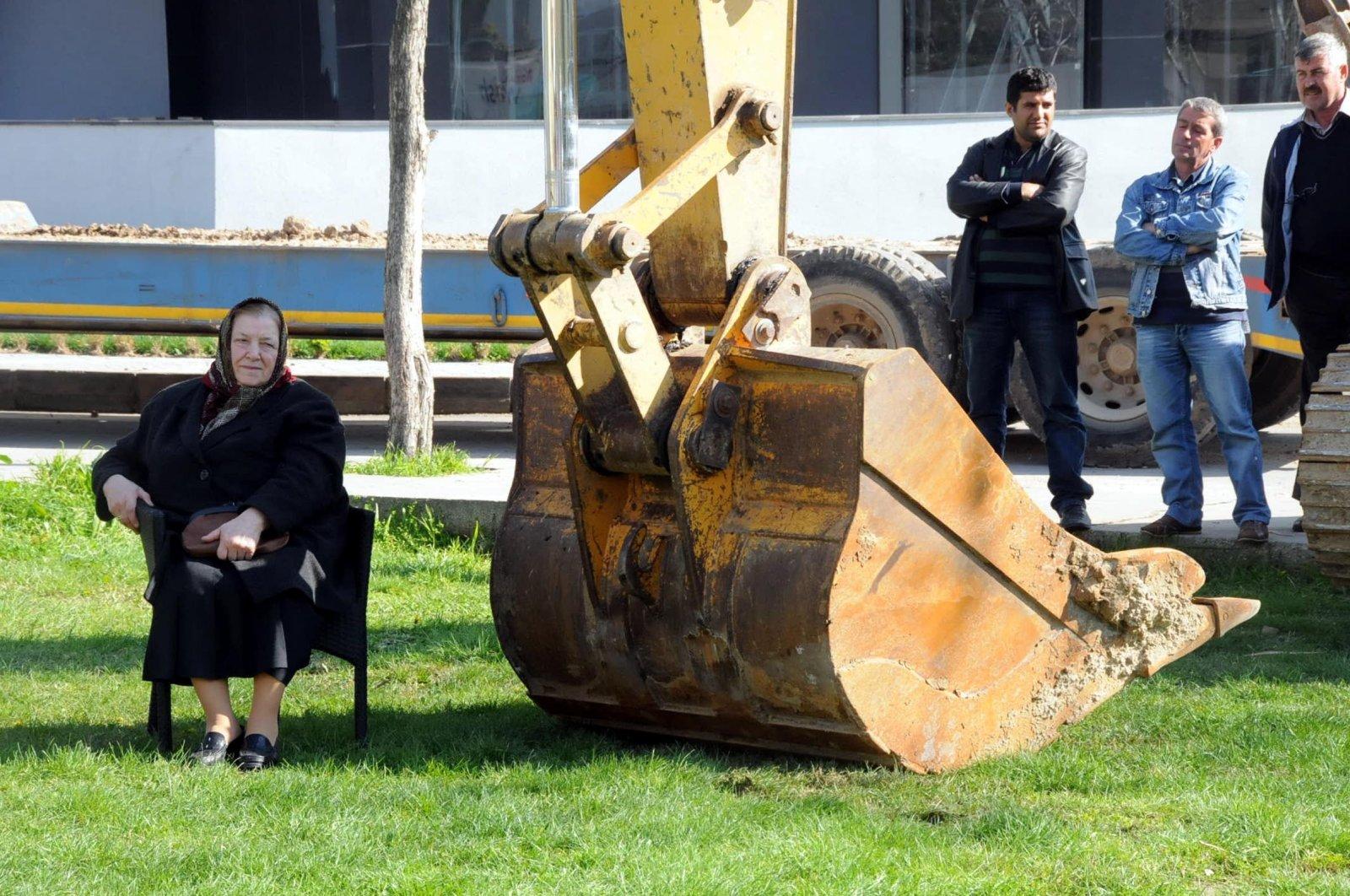 Kıymet Peker sits in front of a bulldozer, in Edirne, northwestern Turkey, March 31, 2014. (DHA PHOTO)