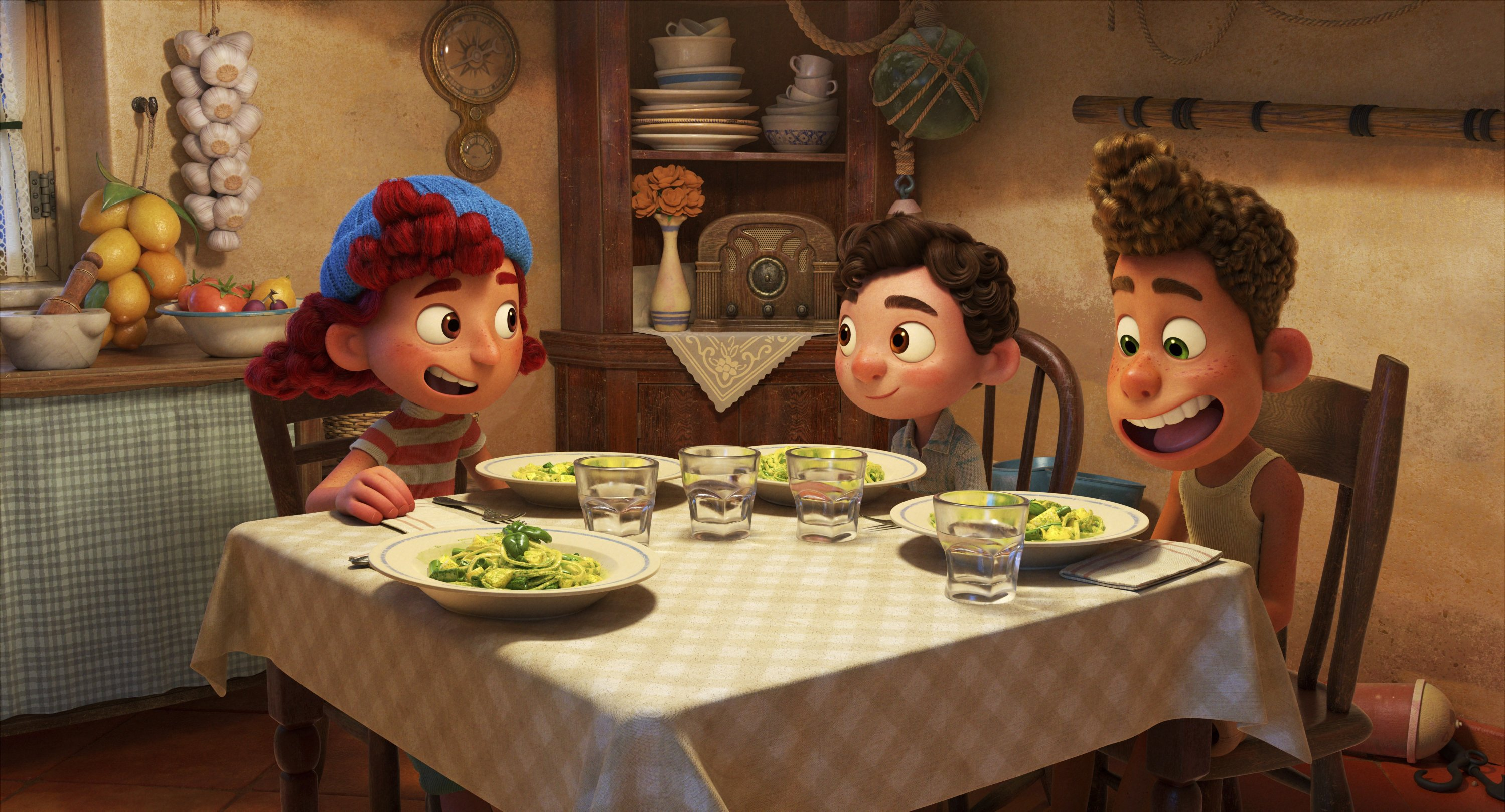 Giulia, voiced by Emma Berman (L), Luca, voiced by Jacob Tremblay (C) and Alberto, voiced by Jack Dylan Grazer, sit around at a table in a scene from the animated film 'Luca.' (Photo by Disney via AP)