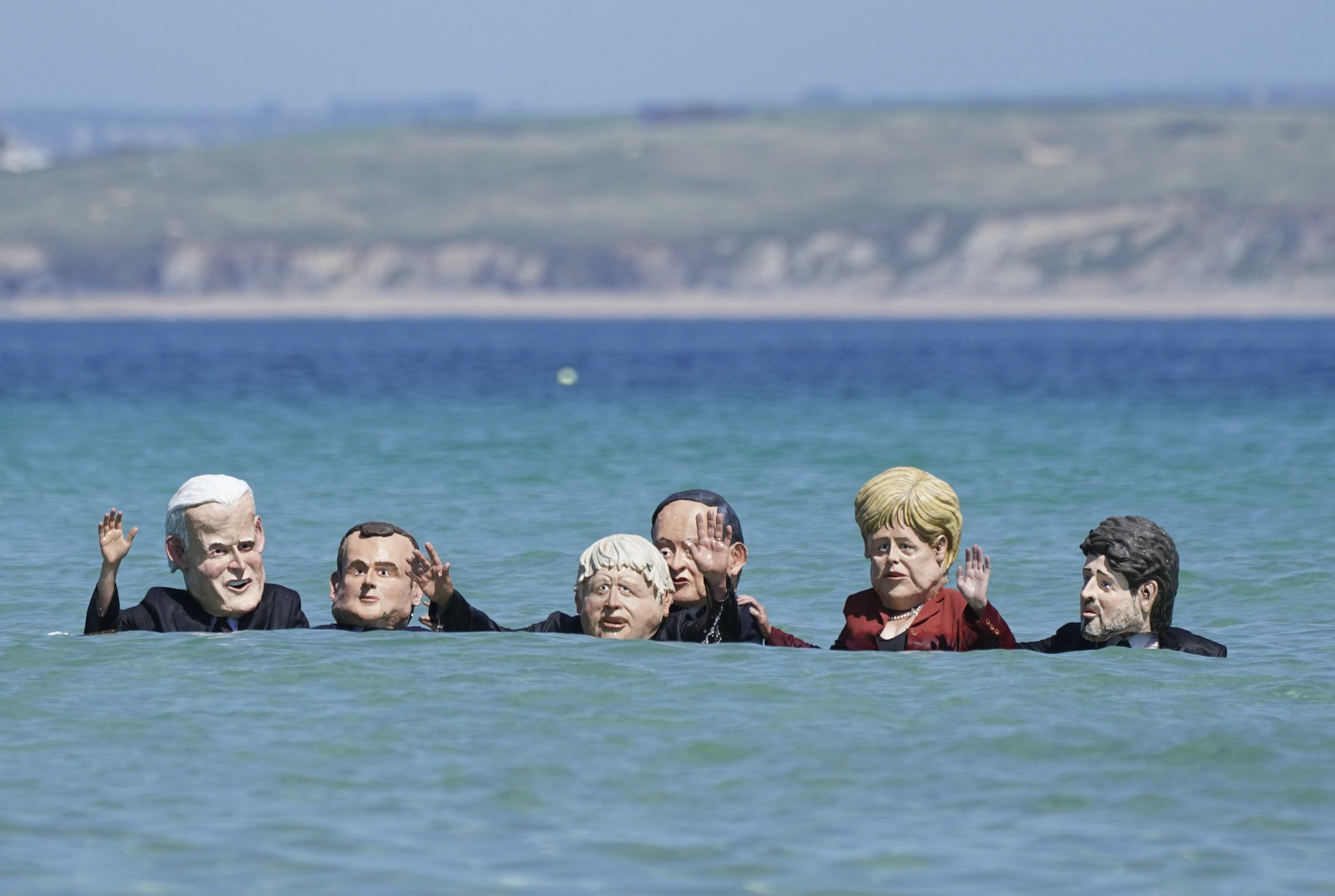 Protestors wearing giant heads portraying G-7 leaders swim in the water during a demonstration outside the G-7 meeting in St. Ives, Cornwall, U.K., June 13, 2021. (AP Photo)