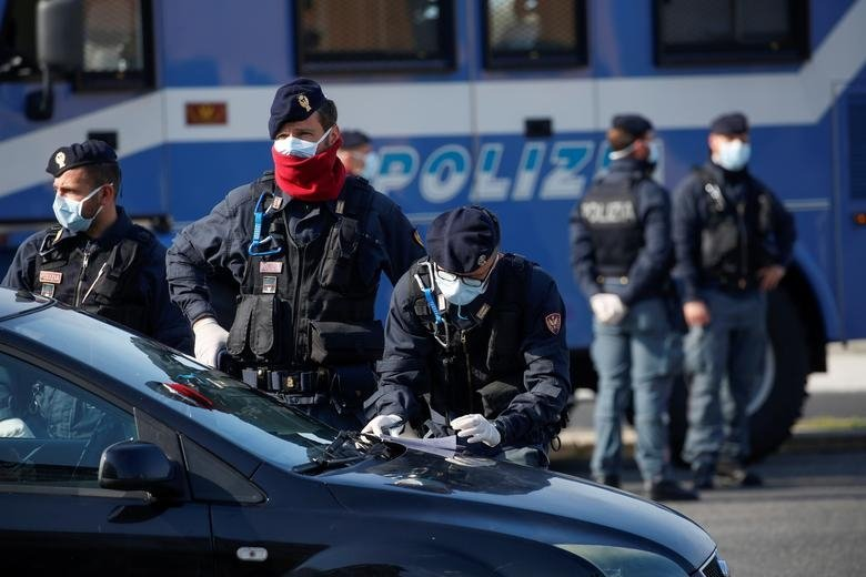 Police officers wearing protective face masks check documents of drivers COVID-19 outbreak in Ostia, near Rome, Italy, April 13, 2020. (Reuters File Photo)