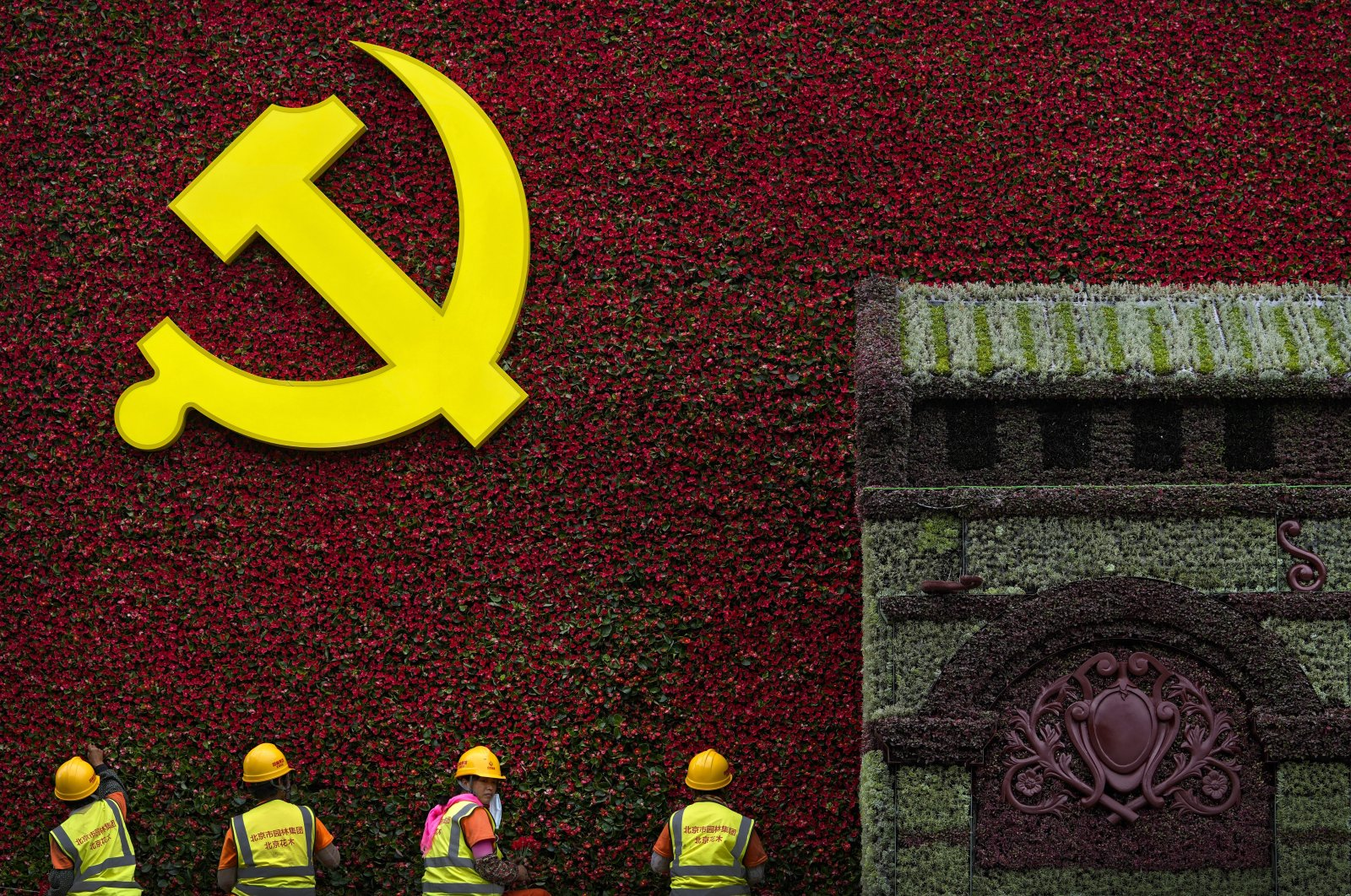 Workers install flowers on a decoration with the Communist Party's logo in Beijing, China, June 16, 2021. (AP Photo)