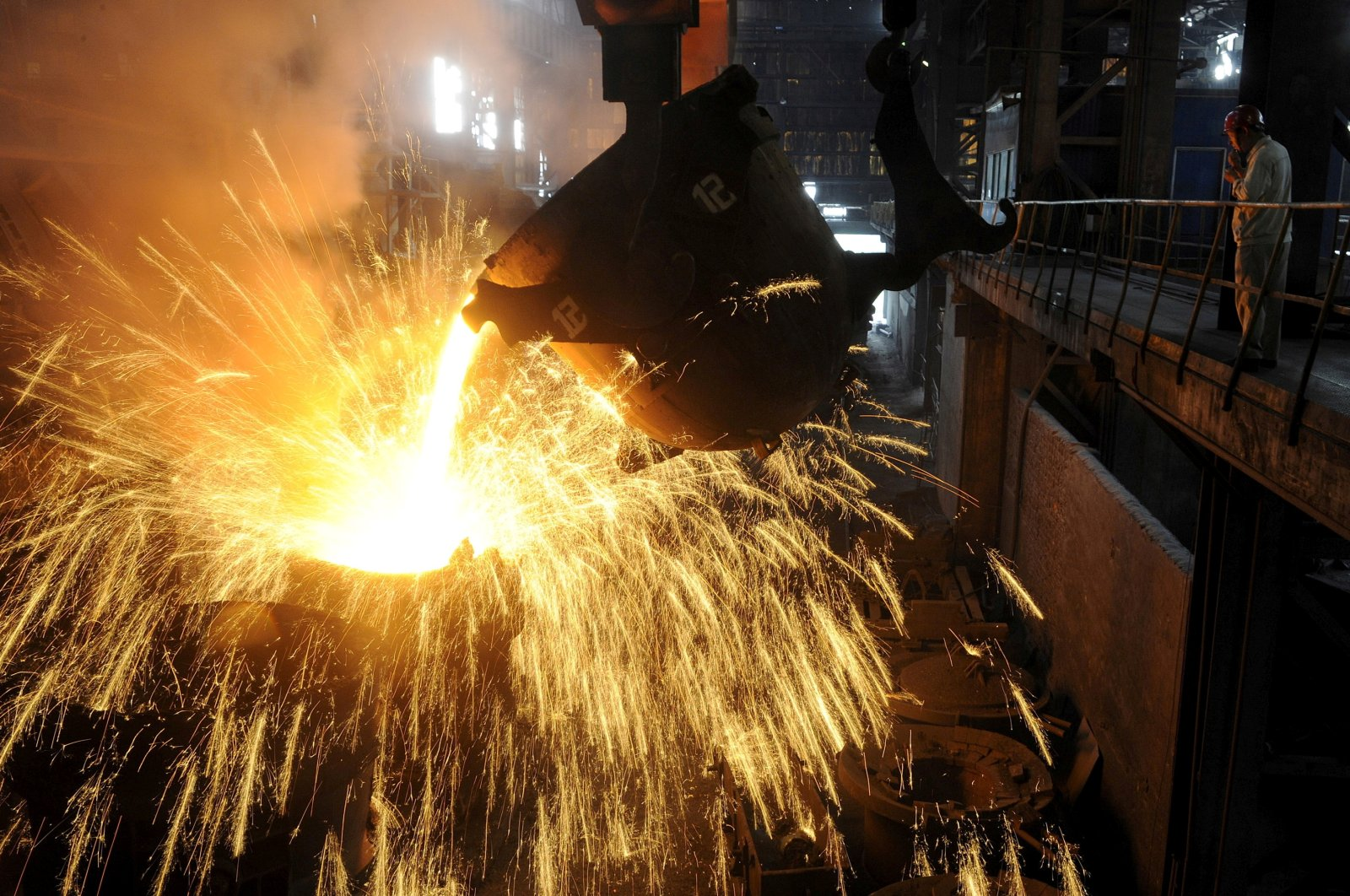 An employee monitors molten iron being poured into a container at a steel plant in Hefei, Anhui province, China, Sept. 9, 2013. (Reuters Photo)