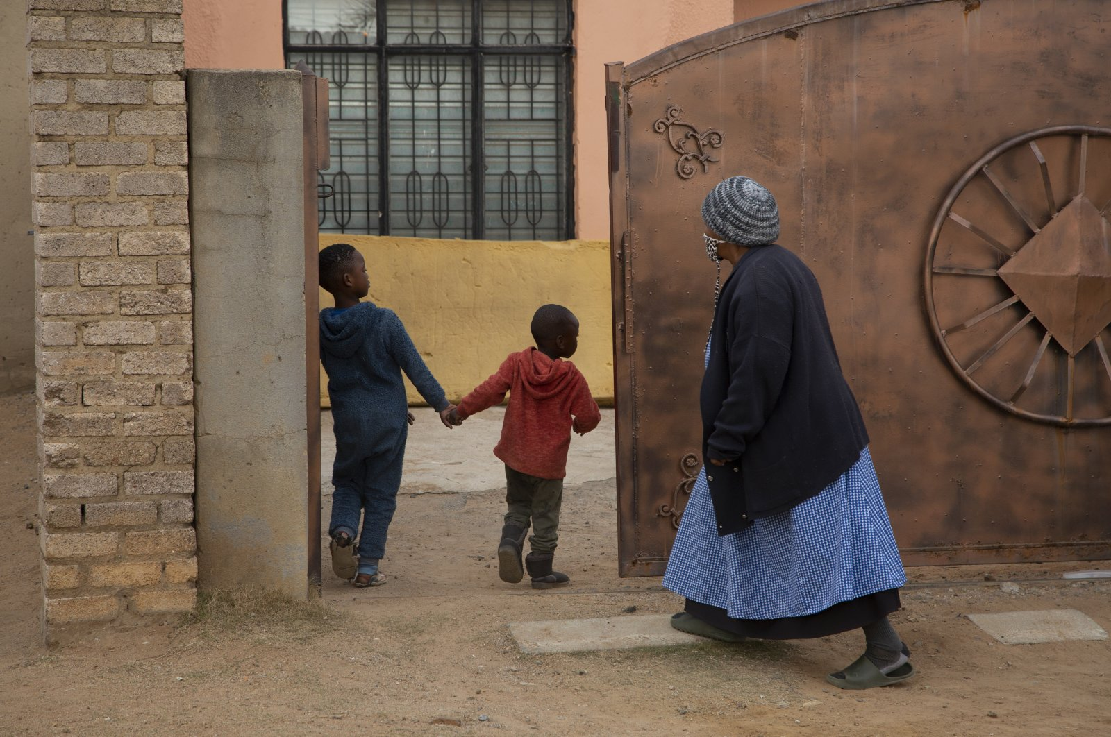 An elderly woman and children enter the property of the home of Gosiame Thamara Sithole in Tembisa, near Johannesburg, South Africa, June 10, 2021. (AP Photo)
