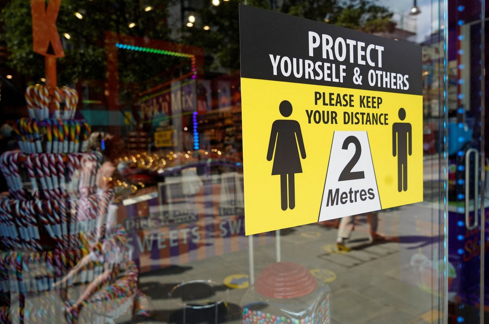 A sign outside a shop asks customers to social distance on Oxford Street in central London, the U.K., June 7, 2021. (AFP Photo)