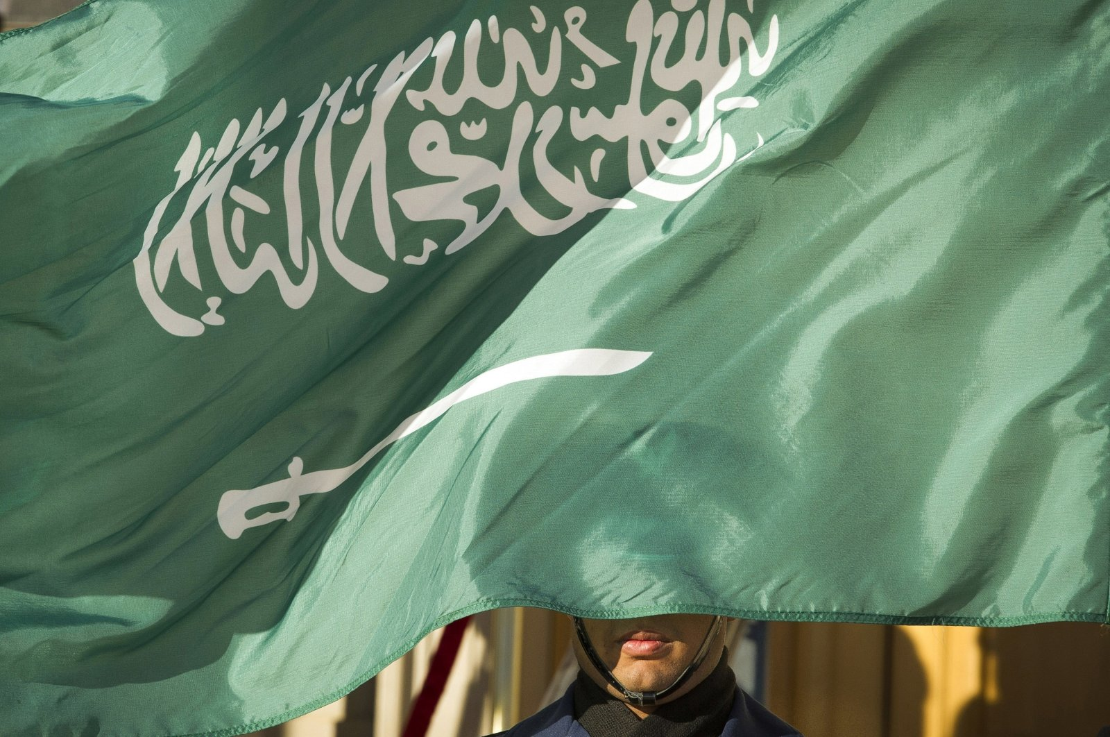 A guard member is covered by the flag of Saudi Arabia in Washington D,C., U.S., June 15, 2021. (AP Photo)