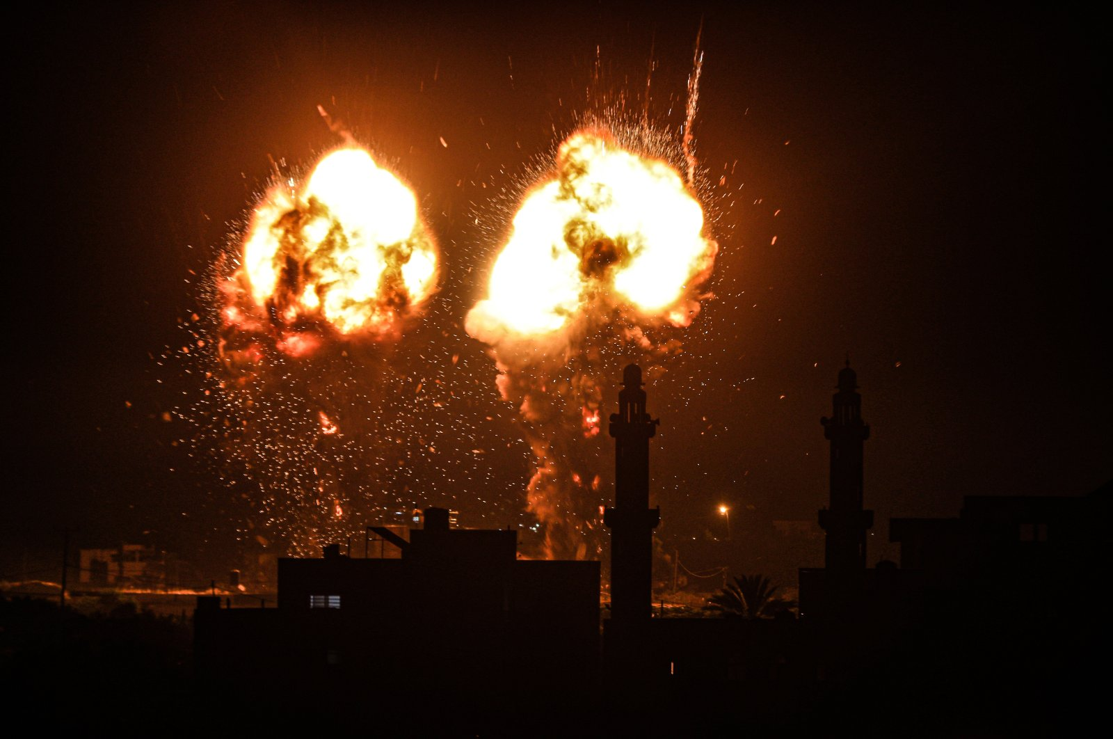 Explosions light up the night sky above buildings in Gaza City as Israeli forces shell the Palestinian enclave, early on June 16, 2021. (AA Photo)