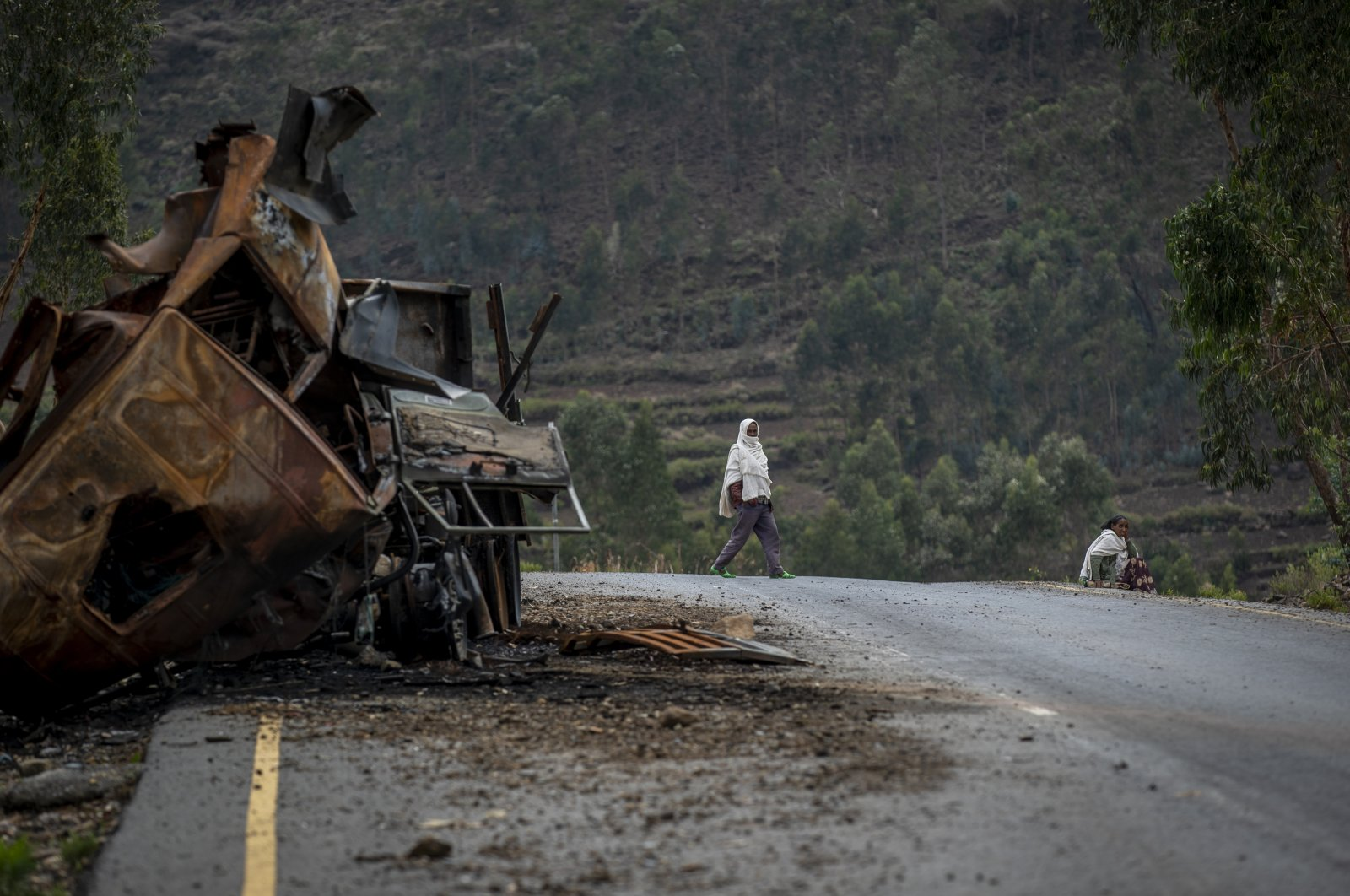 A man crosses near a destroyed truck on a road leading to the town of Abi Adi, in the Tigray region of northern Ethiopia, May 11, 2021. (AP Photo)