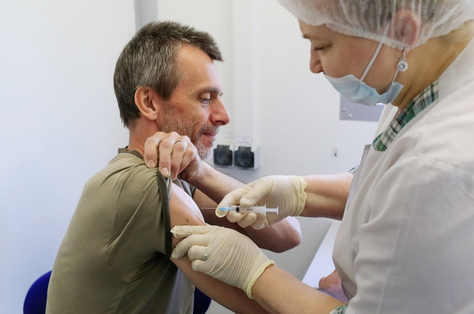 A man receives a dose of Sputnik V vaccine against the coronavirus at a mobile vaccination center in a dacha community near the village of Poyarkovo in Moscow Region, Russia, May 31, 2021. (Reuters Photo)