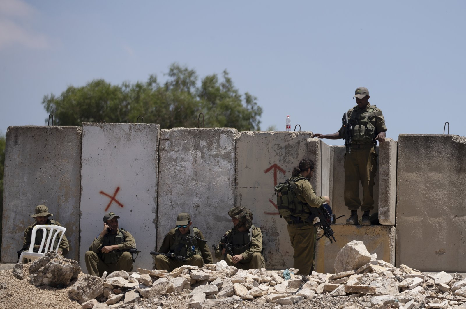 Israeli soldiers rest at the site of a vehicle attack near Hizma in the occupied West Bank, June 16, 2021. (AP Photo)