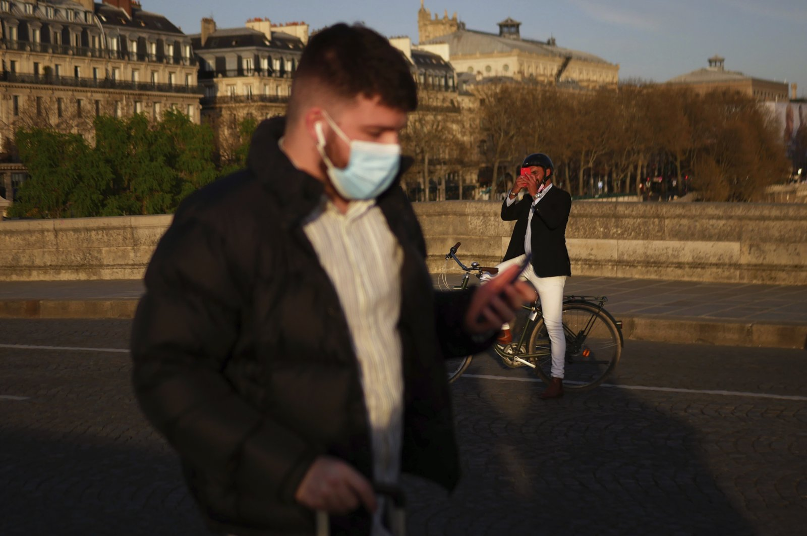 A man walks with a face mask to prevent the spread of the COVID-19 coronavirus, as a man takes a snapshot of the sunset, in Paris, March 29, 2021. (AP Photo)