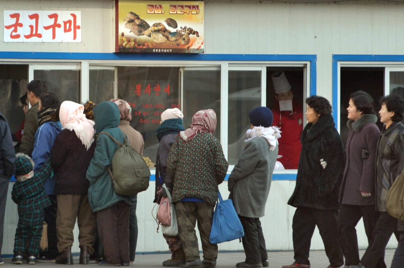 People line up in front of a food store in Pyongyang, North Korea, Nov. 26, 2010. (Reuters Photo/Kyodo)