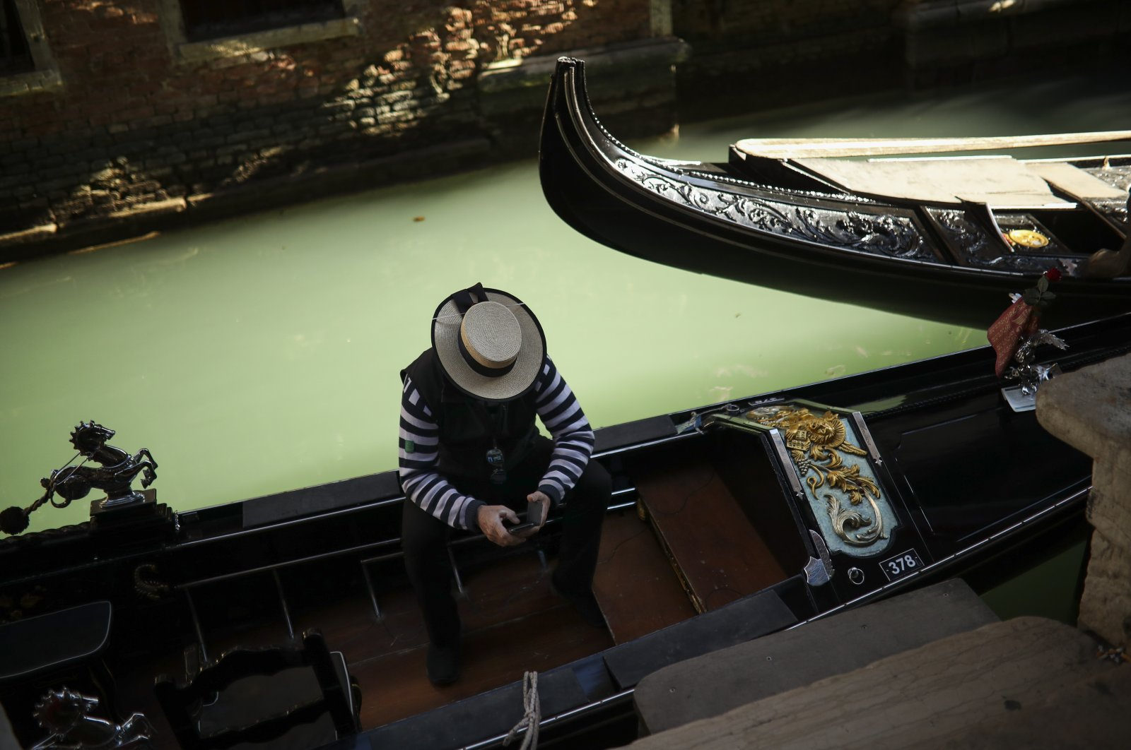 A gondolier looks at his smartphone as he waits for clients in Venice, Italy, Feb. 28, 2020. (AP Photo)