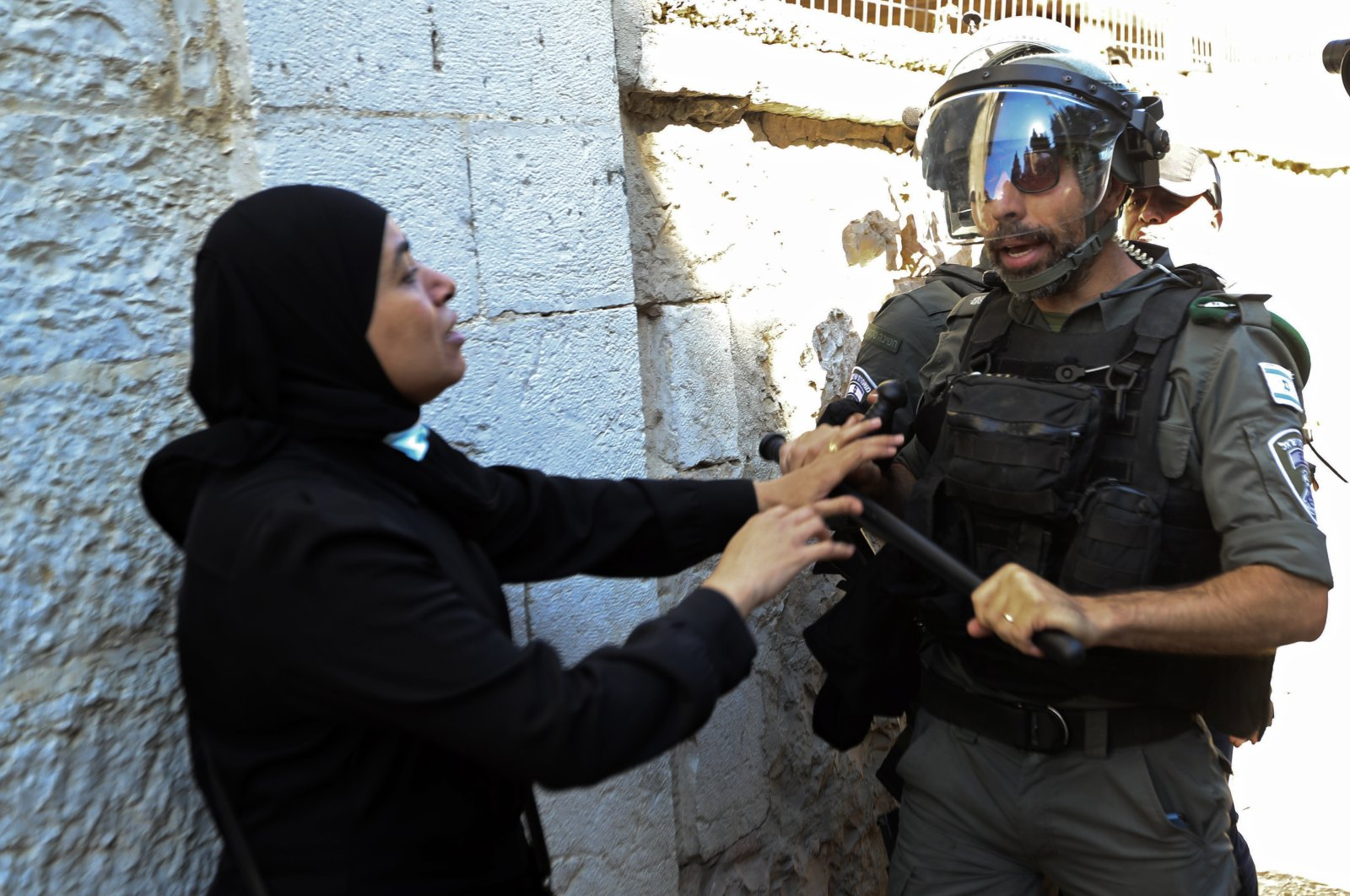 An Israeli police officer and a Palestinian woman scuffle during clashes that erupted ahead of a planned march by Jewish ultranationalists through East Jerusalem, outside Jerusalem's Old City, Tuesday, June 15, 2021. (AP Photo)