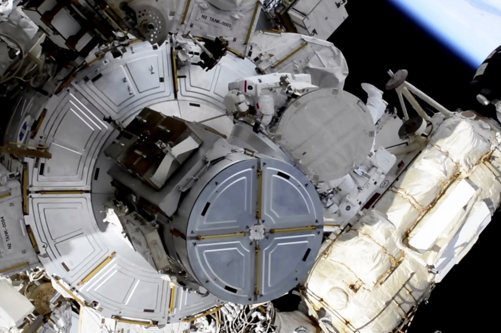In this image taken from NASA video, French astronaut Thomas Pesquet, top center, and NASA astronaut Shane Kimbrough venture out on a spacewalk Wednesday, June 16, 2021. (NASA via AP)