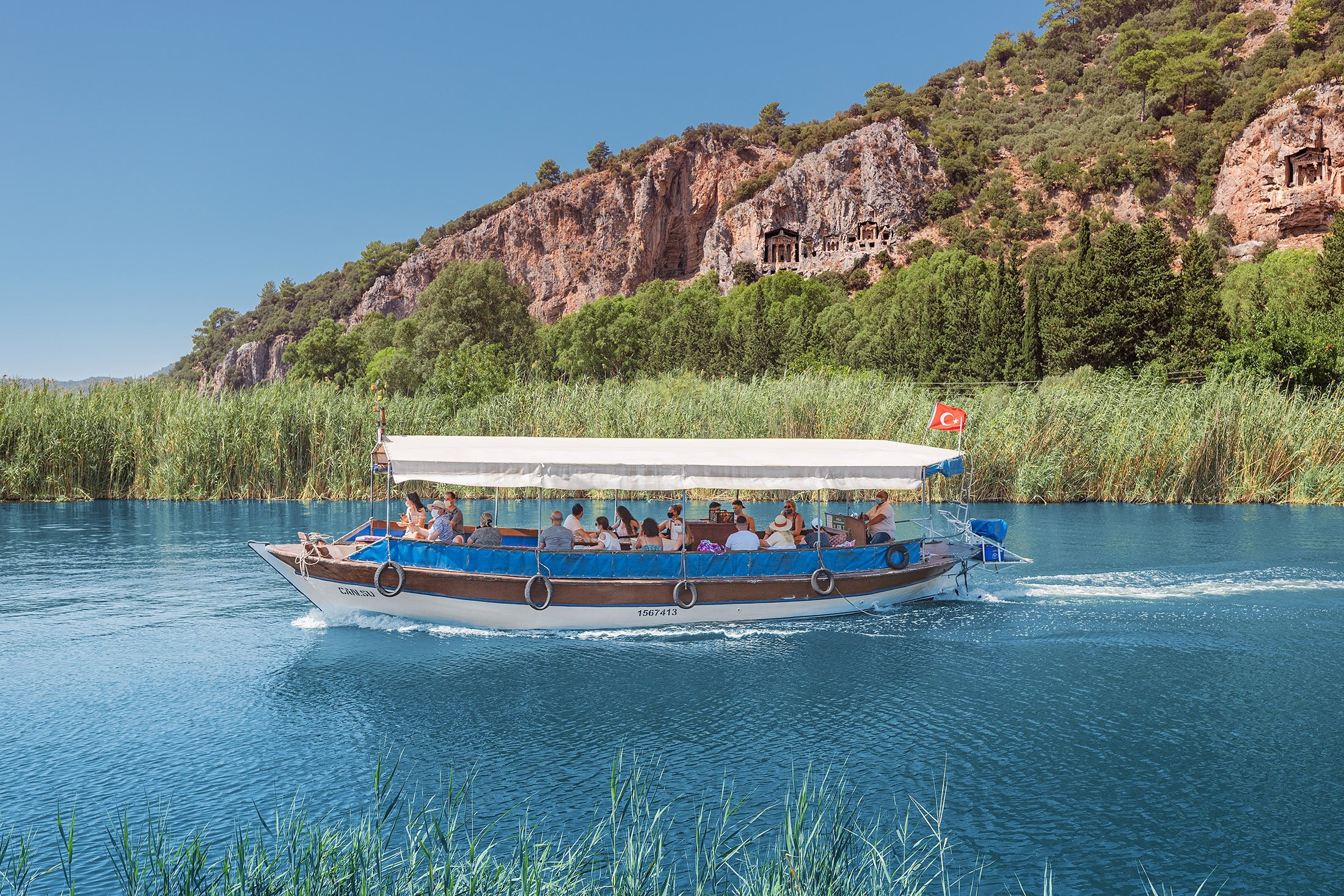 Cruise ships and ferry boats with Turkish flags transport tourists to the Dalyan river delta and the ancient city of Kaunos. (Shutterstock Photo)