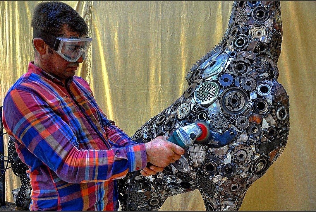 Mervan Altınorak, a mosaic and sculpture artist, works on a sculpture of a giraffe created with scrap metals, Hatay, Turkey, June 16, 2021. (IHA Photo)