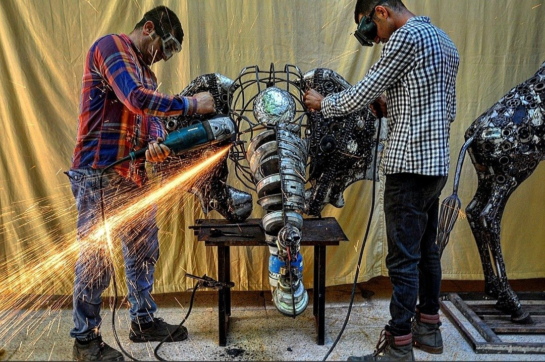 Mervan Altınorak (L) works on a sculpture of an elephant created with scrap metals, with an assistant, Hatay, southern Turkey, June 16, 2021. (IİHA Photo)