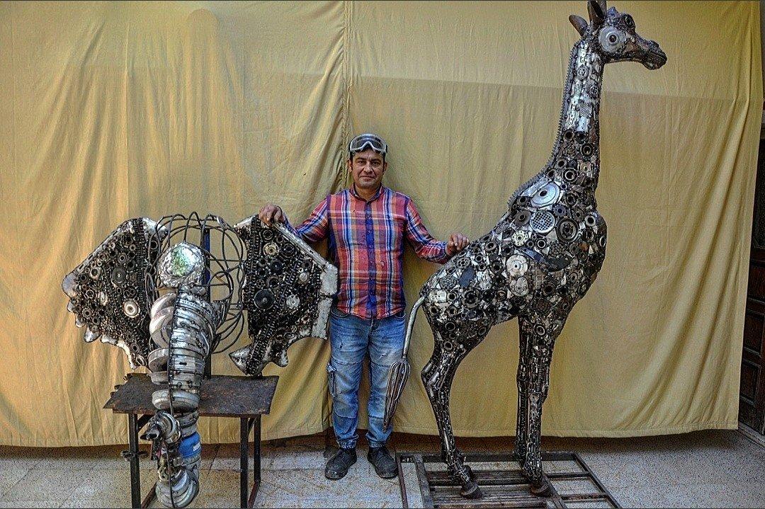 Mervan Altınorak, a mosaic and sculpture artist, poses with sculptures of a giraffe and an elephant, created with scrap metals, Hatay, Turkey, June 16, 2021. (IHA Photo)