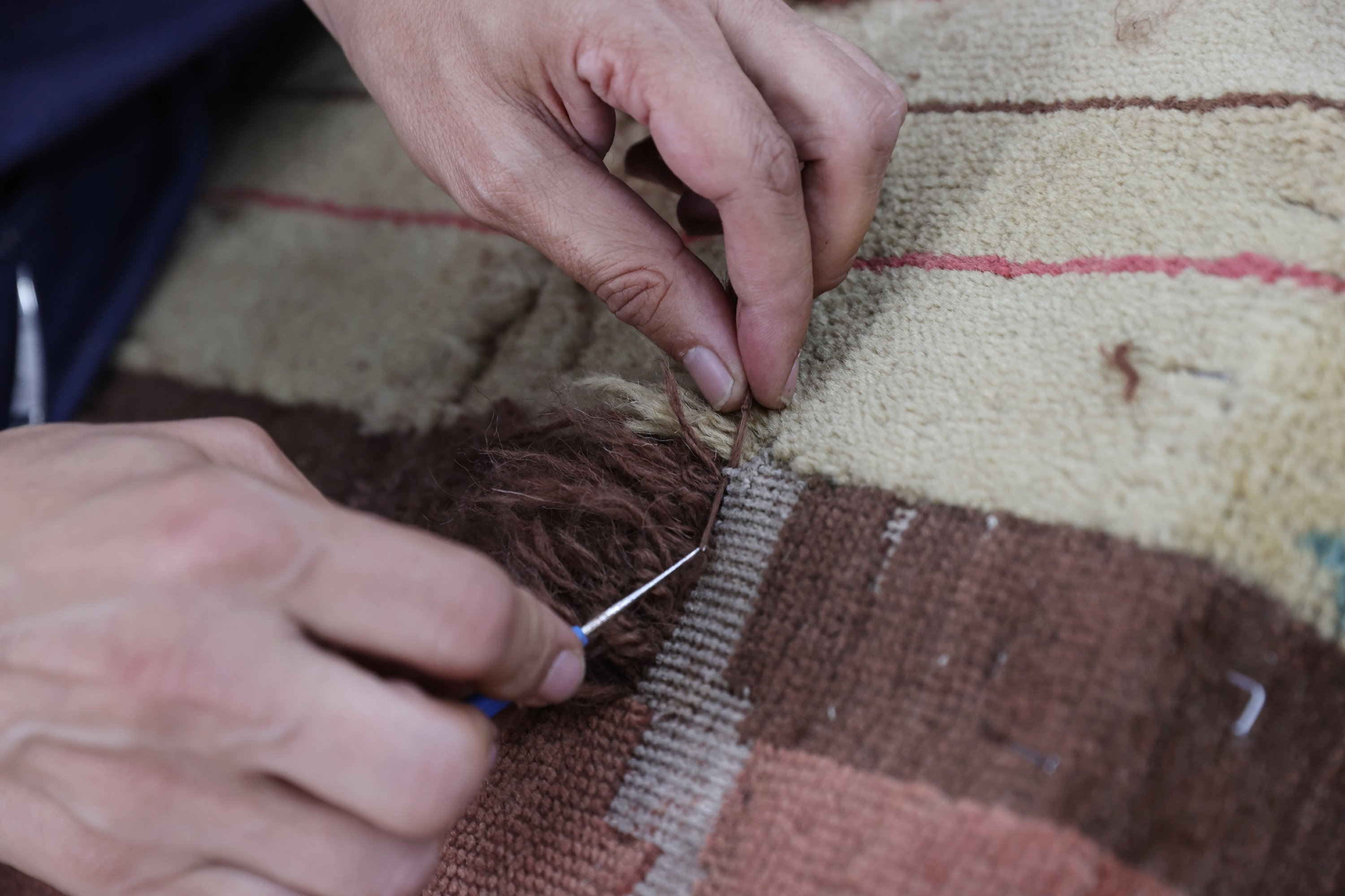 A close-up of the hands of an expert working on the restoration of the carpet in the workshop of the Yıldız Şale Mansion, Istanbul, Turkey, June 17, 2021. (AA Photo)