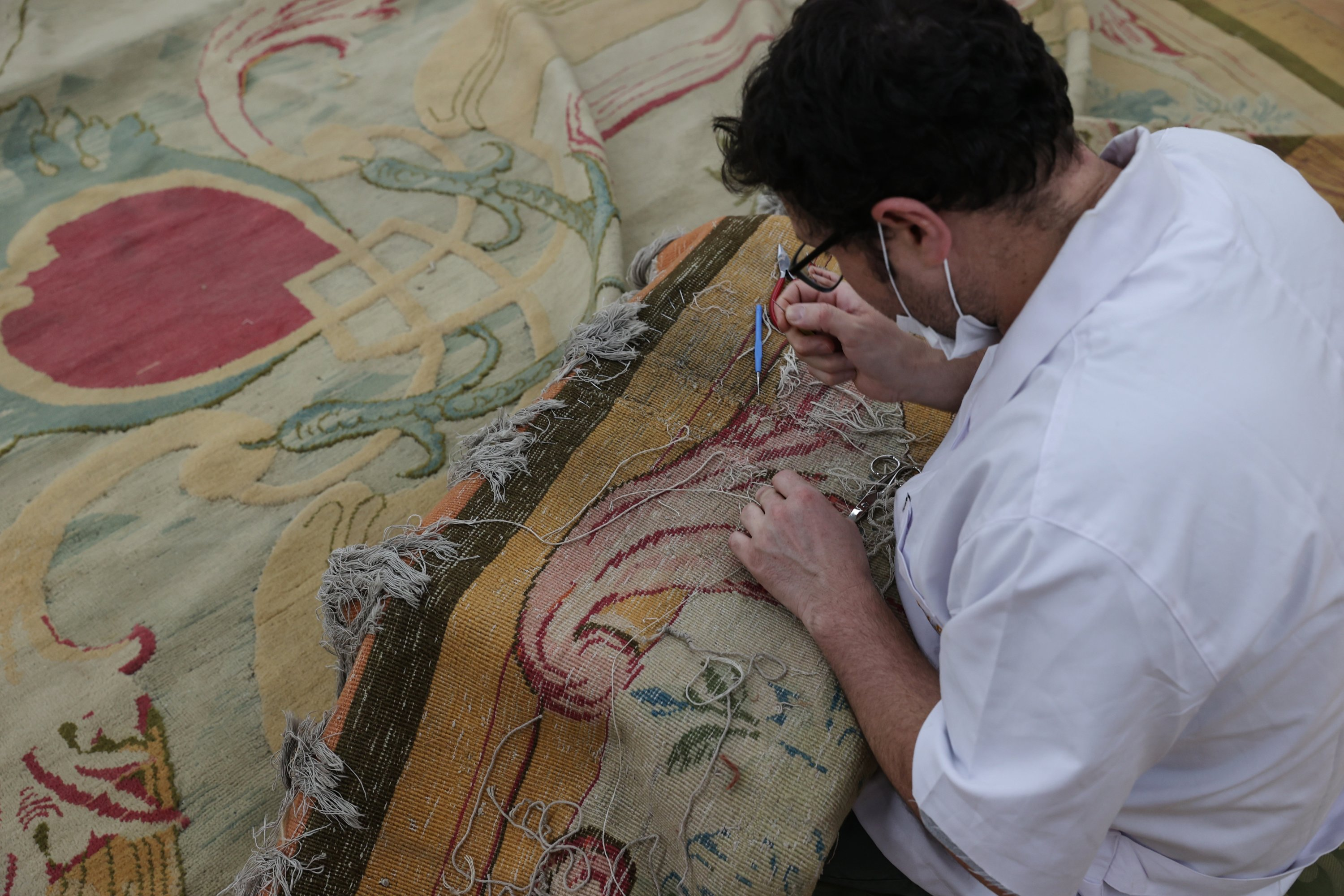 An expert works on the restoration of the carpet in the workshop of the Yıldız Şale Mansion, Istanbul, Turkey, June 17, 2021. (AA Photo)