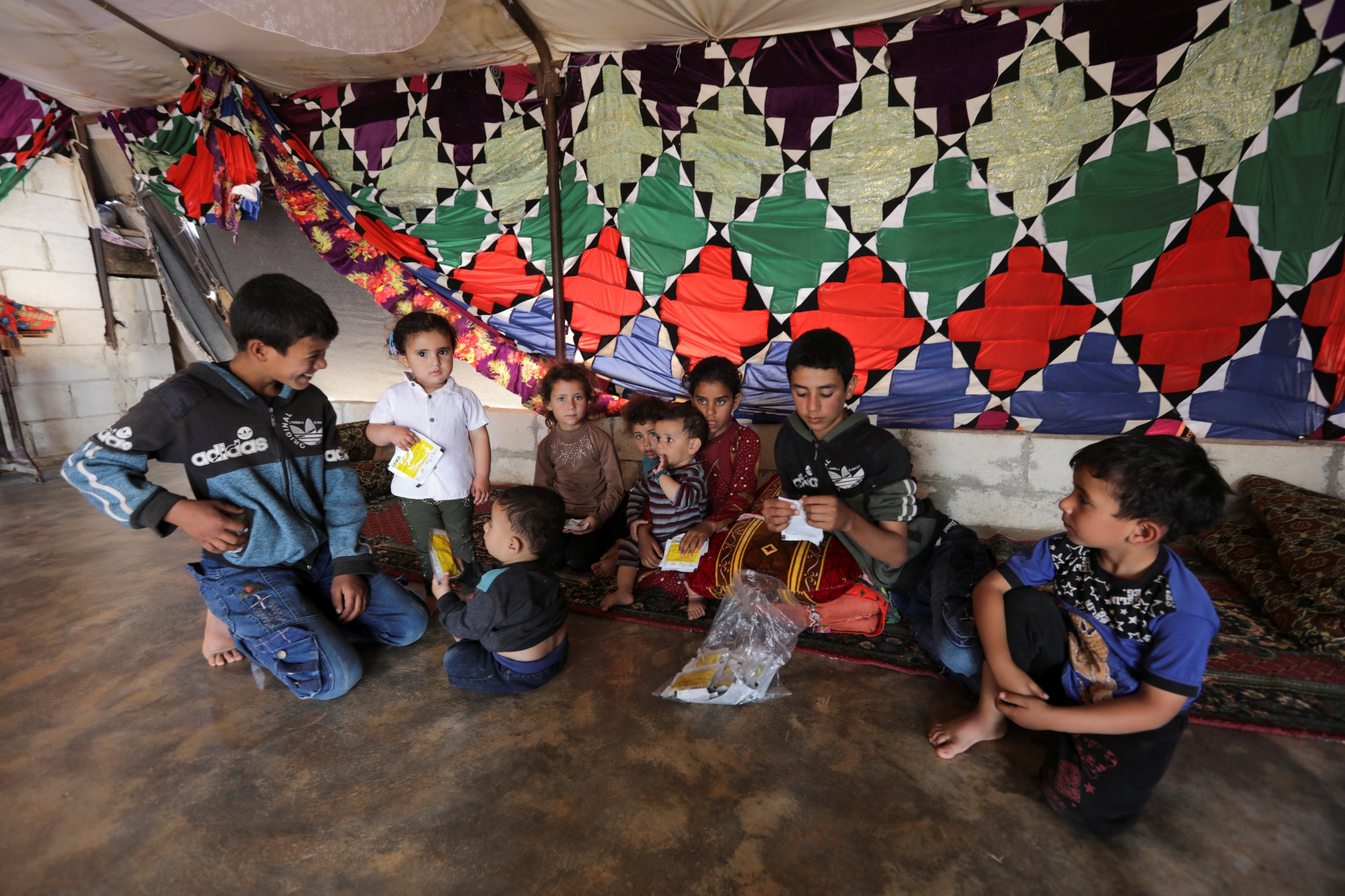 The children of Hussein Mahmoud, an internally displaced farmer, sit together inside a tent in the opposition-held Idlib, Syria, June 9, 2021. (Reuters Photo)