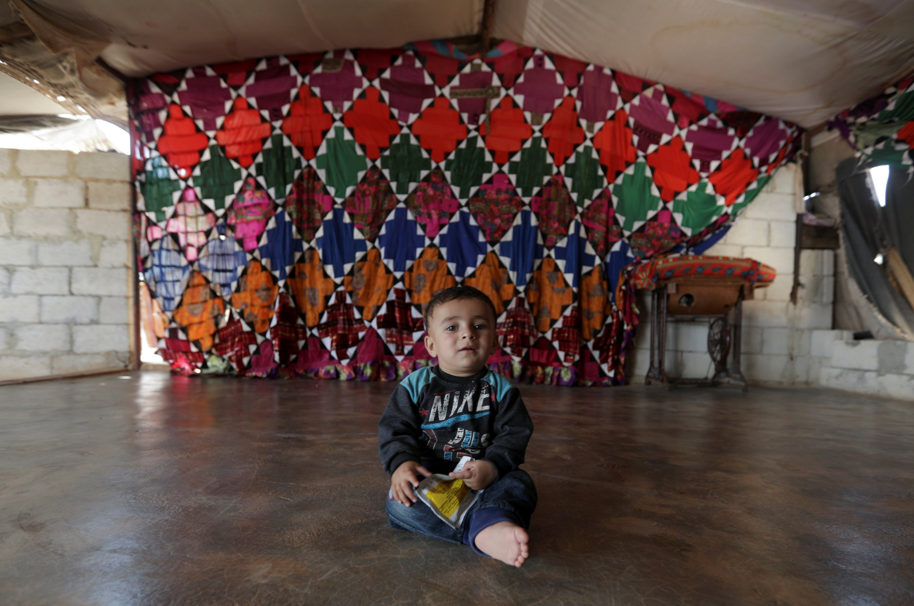 Son of Hussein Mahmoud, an internally displaced farmer, sits inside a tent in the opposition-held Idlib, Syria, June 9, 2021. (Reuters Photo)