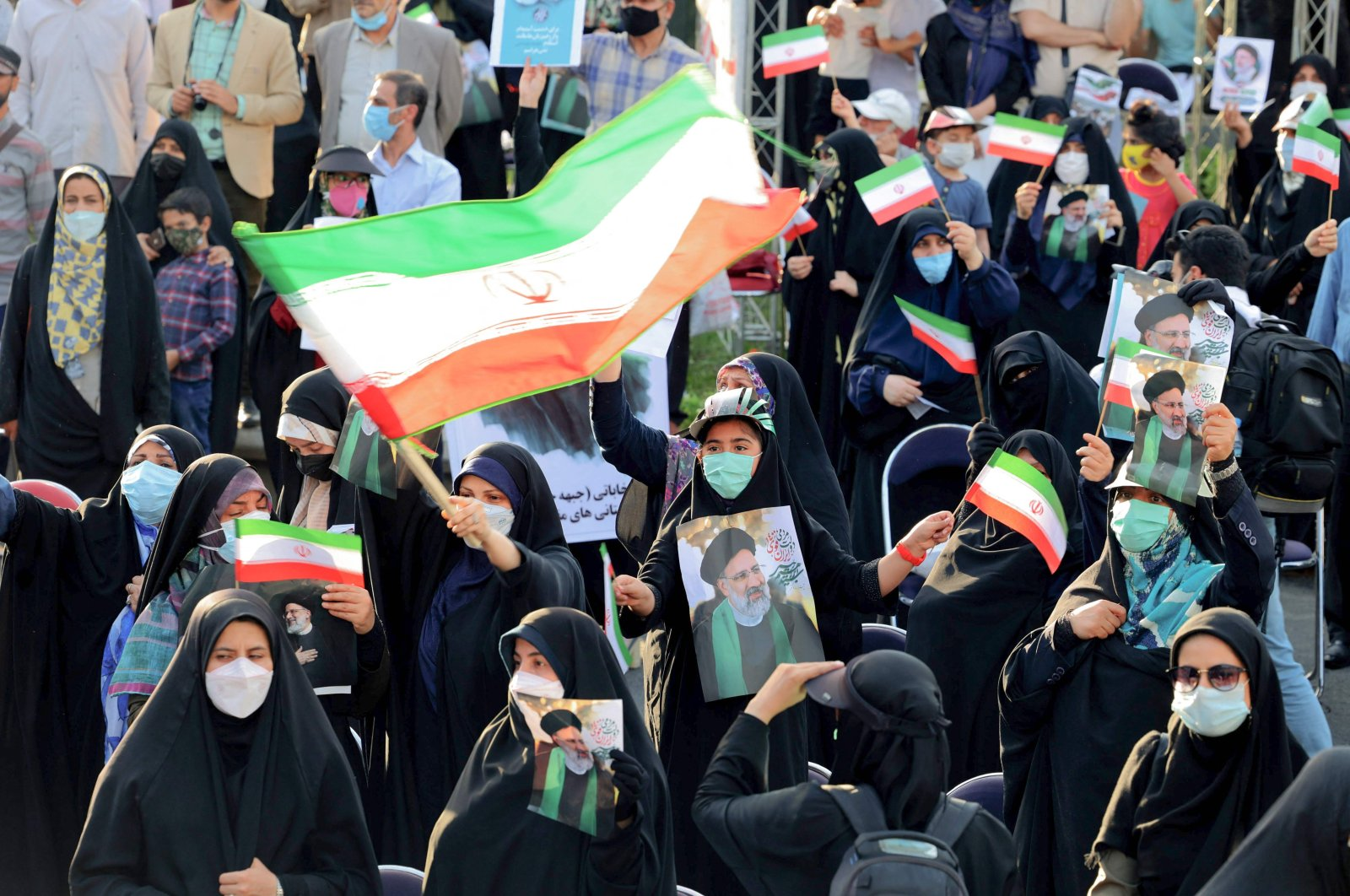 Supporters of Iranian ultraconservative presidential candidate Ebrahim Raisi carry posters bearing his portrait and wave national flags as they attend a rally ahead of the Islamic republic's June 18 presidential election, in the capital Tehran, Iran, June 16, 2021. (AFP Photo)