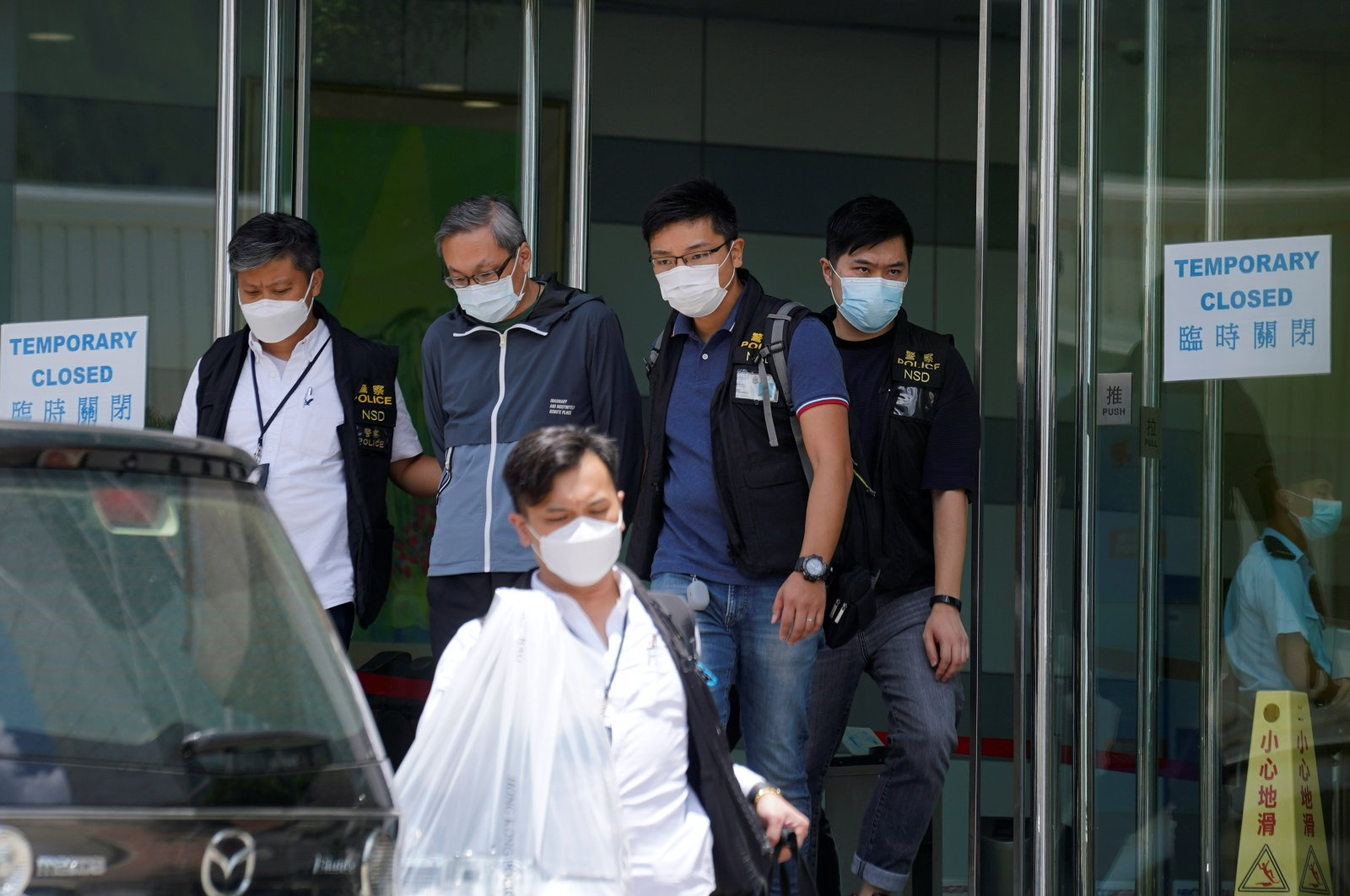 Police officers from Hong Kong's National Security Department escort Apple Daily's Chief Executive Officer Cheung Kim-hung from the offices of Apple Daily and Next Media in Hong Kong, June 17, 2021.(Reuters Photo)